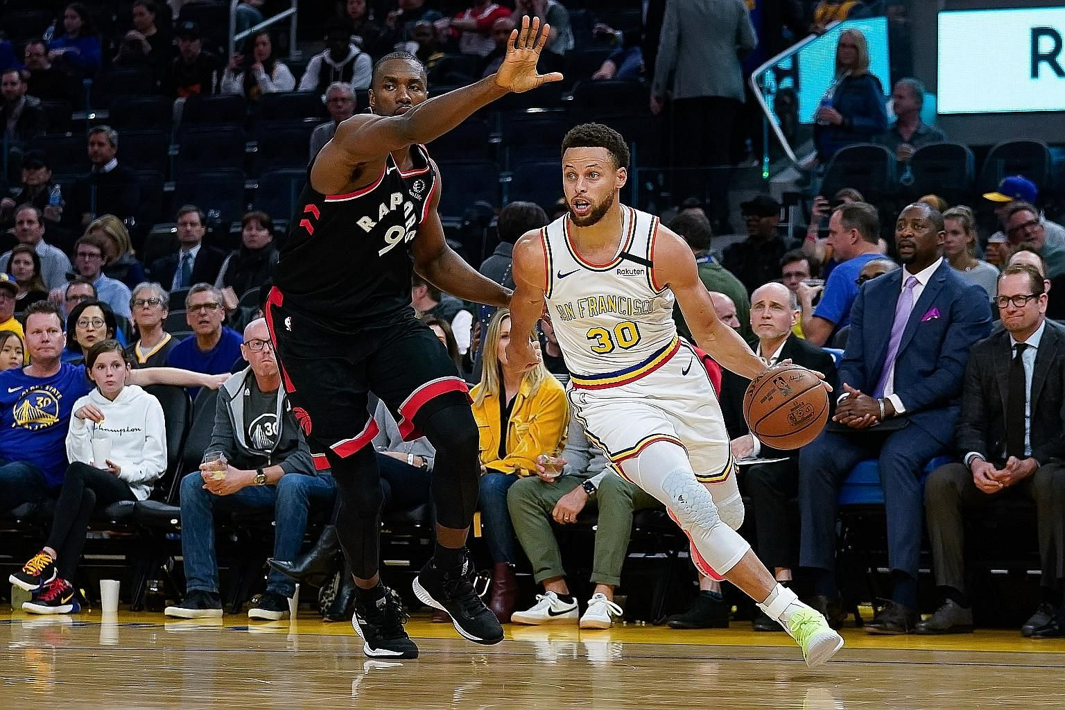 Golden State Warriors guard Stephen Curry (right) driving past Toronto Raptors centre Serge Ibaka on his return to action on Thursday after four months out with a broken hand. But National Basketball Association champions Toronto, led by Norm Powell'