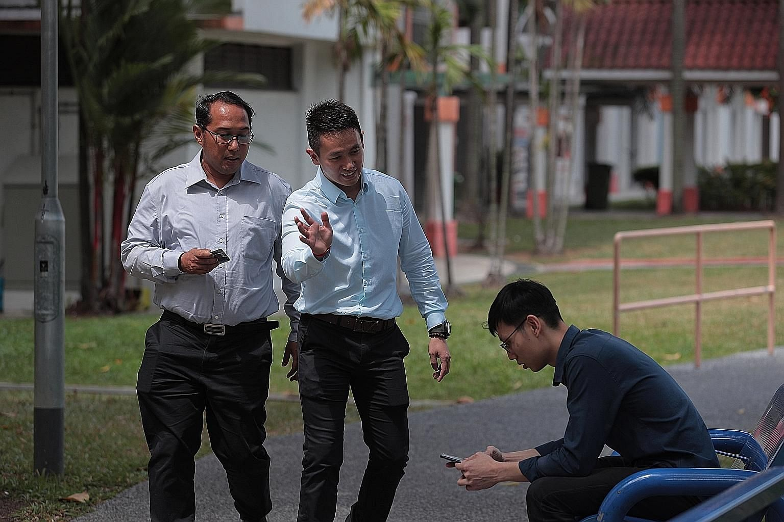 Senior Staff Sergeant Mohamad Shapie Saleh (left) and Sergeant Loh Seng Hong showing how they would conduct interviews in the field. Officers use their usual investigative methods to hunt down close contacts - analysing surveillance footage and speak