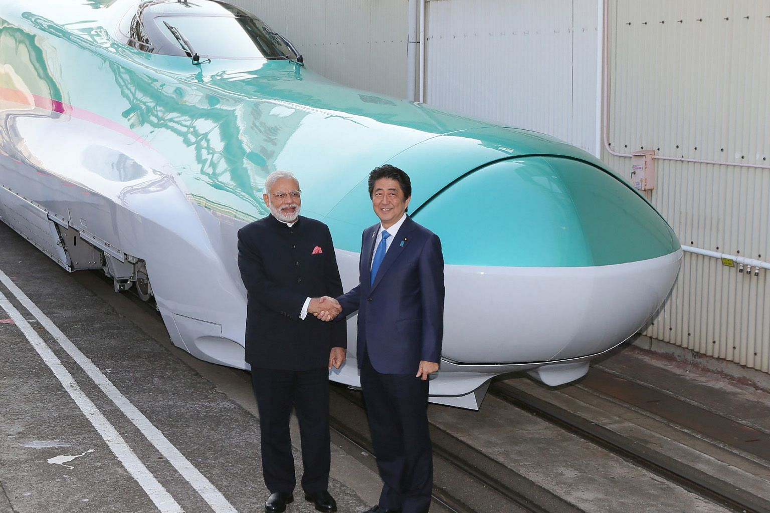 Indian Prime Minister Narendra Modi and his Japanese counterpart Shinzo Abe with a shinkansen train in Kobe, Japan, in this 2016 picture. India's high-speed rail project is developed with the Japanese.