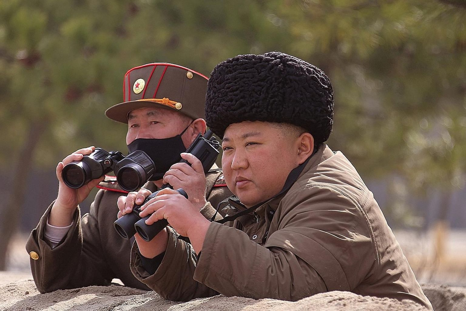 """Mr Kim Jong Un (above), in a photo released on Monday by the North Korean state news agency, was at the firepower strike drill (left) with commanders of the Korean People's Army. He had expressed """"great satisfaction with the result"""". PHOTOS: REUTERS,"""