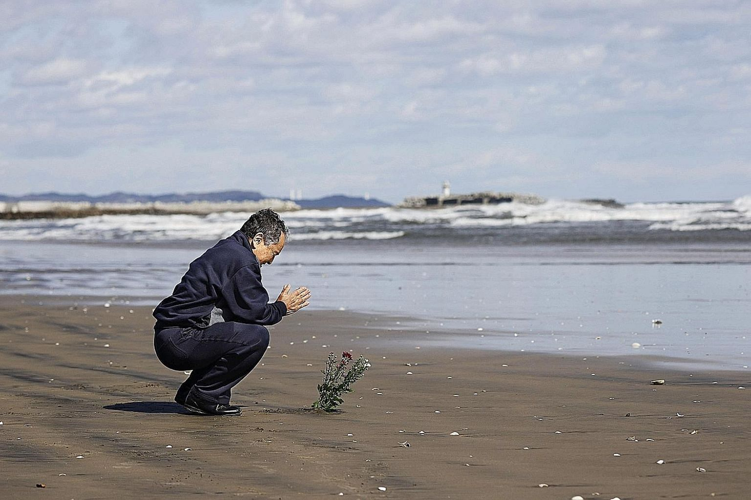A man offering prayers by the sea in Minamisoma in memory of those killed by the Fukushima disaster of nine years ago. A man praying on the beach in Iwaki as Japan marked the anniversary of the Fukushima disaster. Across Japan, people observed a minu