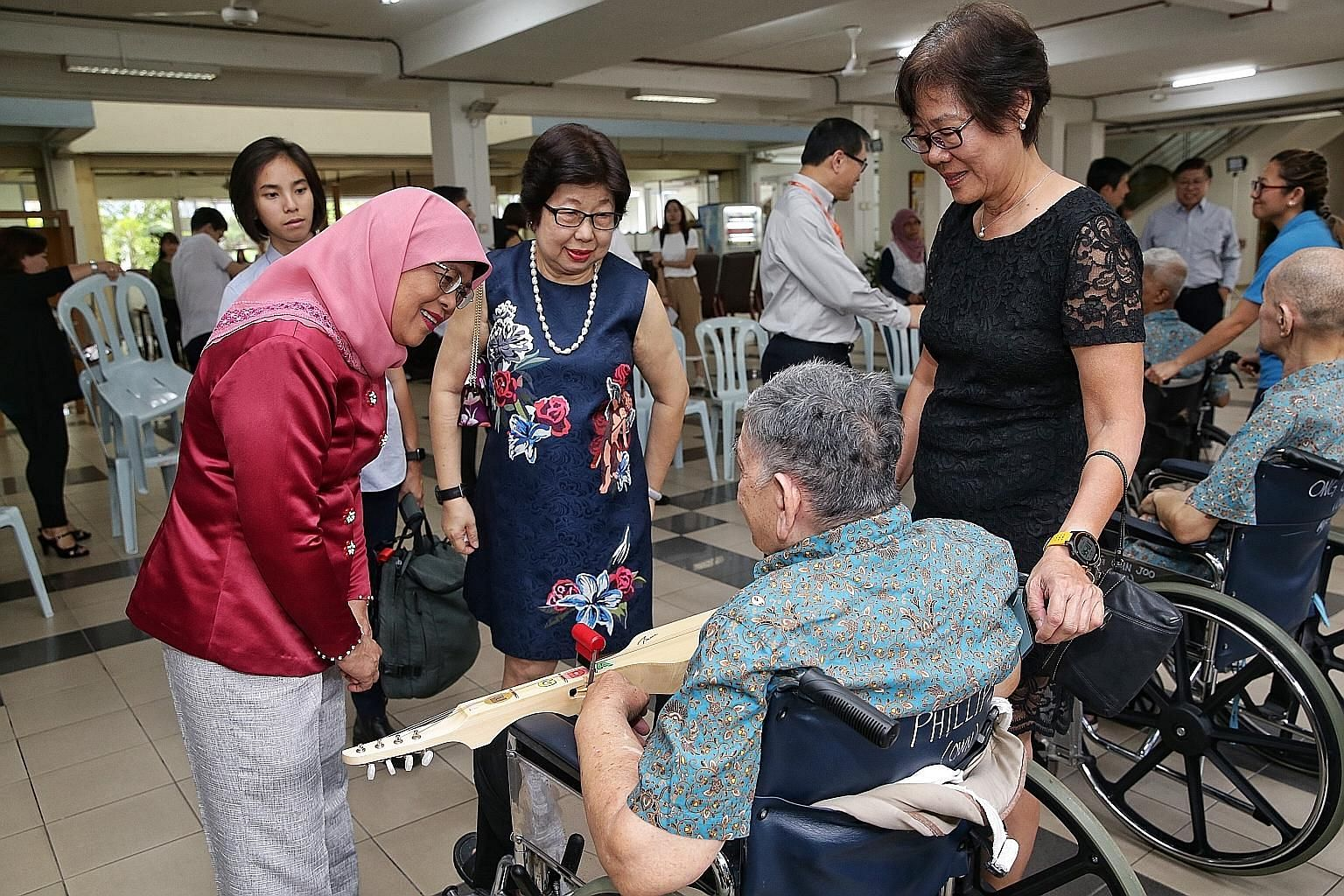 President Halimah Yacob, accompanied by Ling Kwang Home for Senior Citizens executive committee member Angelina Chua (centre) and director of nursing Lee Geok Yian (right), interacting with a senior citizen who participated in a music performance at