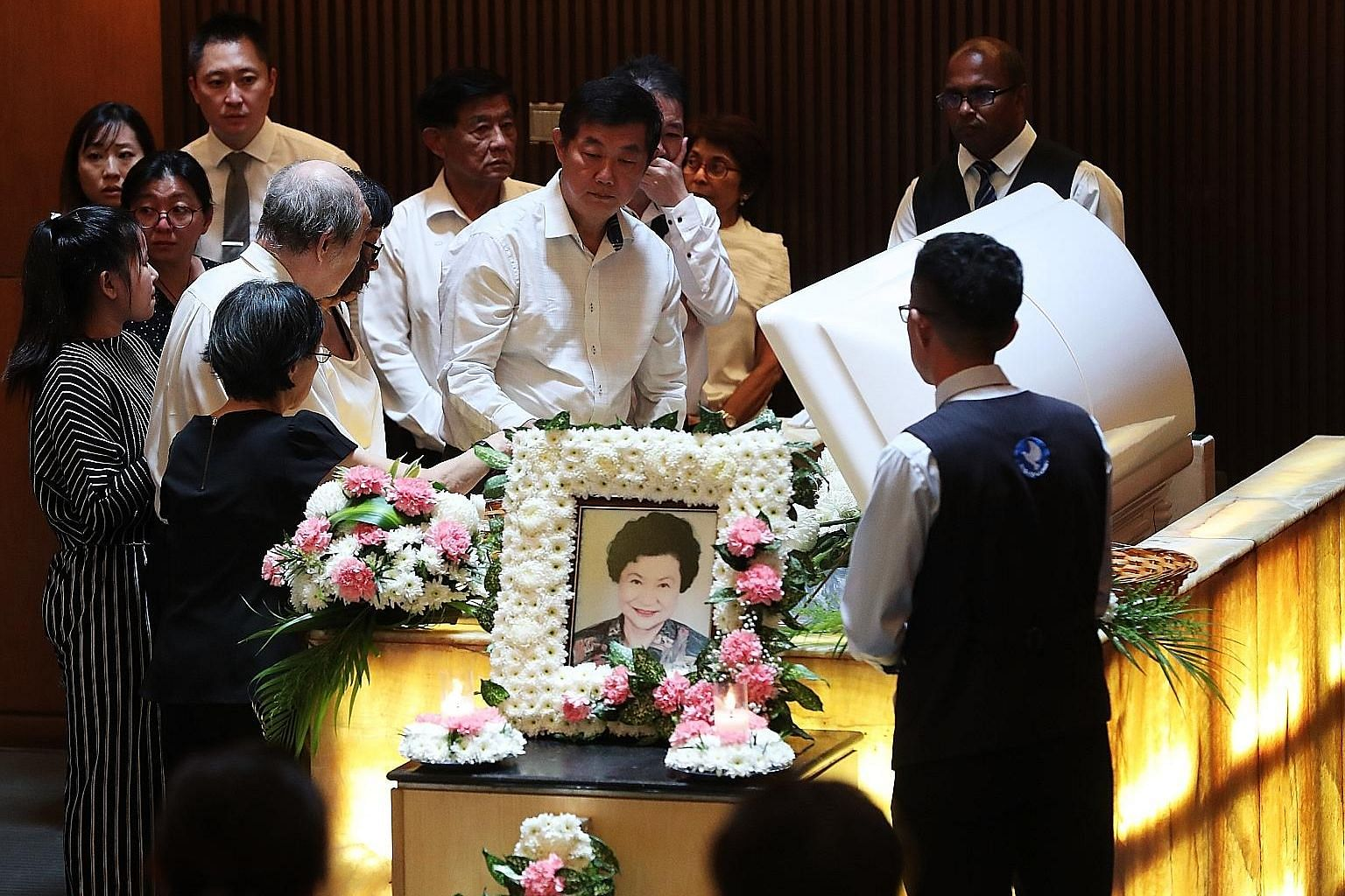 Madam Kwei's sons Nelson Kwei (centre) and Michael Chen (left of Nelson) at their mother's funeral in Mandai Crematorium yesterday.