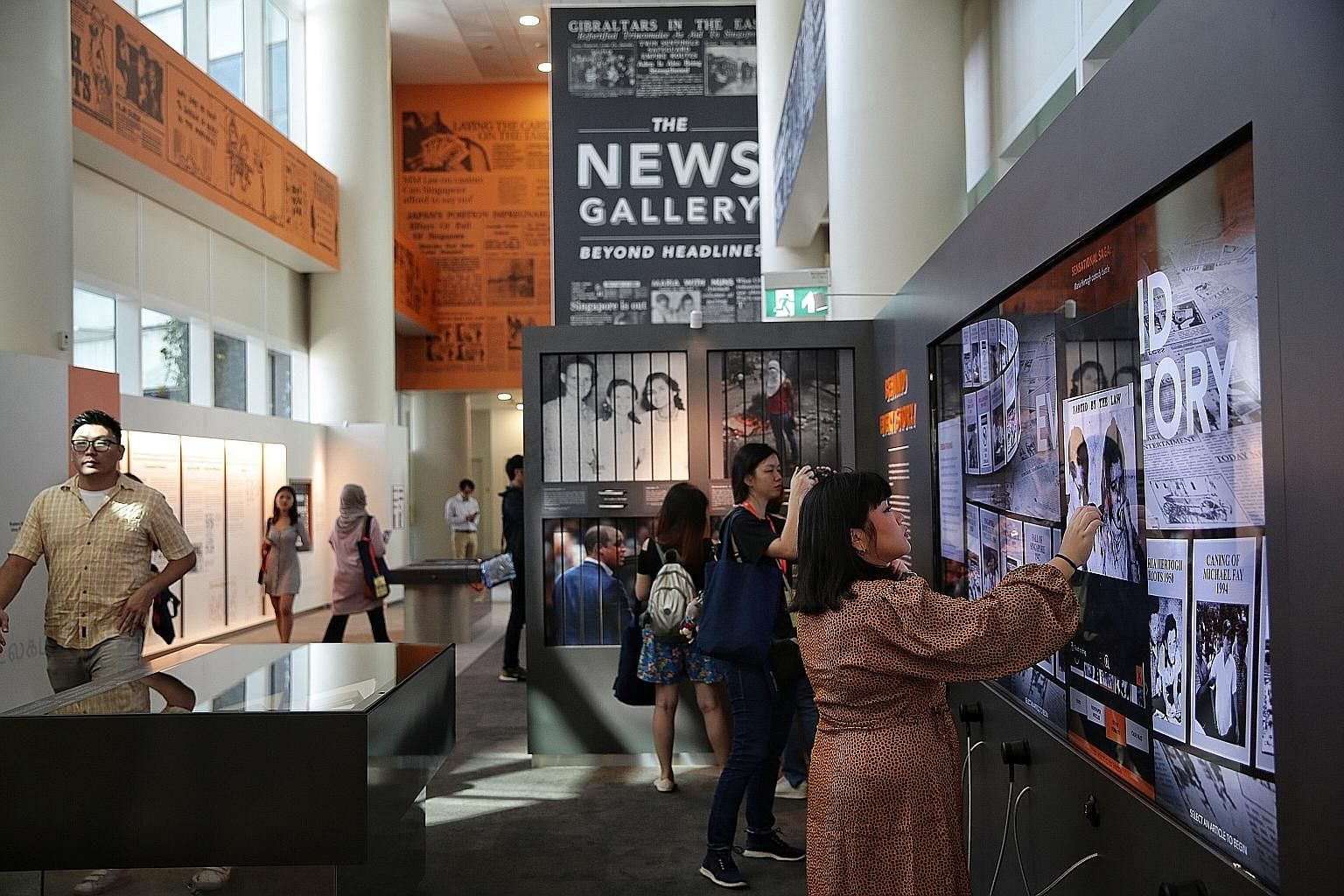 Invited guests exploring the National Library's new permanent exhibition, called The News Gallery: Beyond Headlines, yesterday. It includes interactive screens showing how different newspapers covered events in the nation's past, such as the Maria He