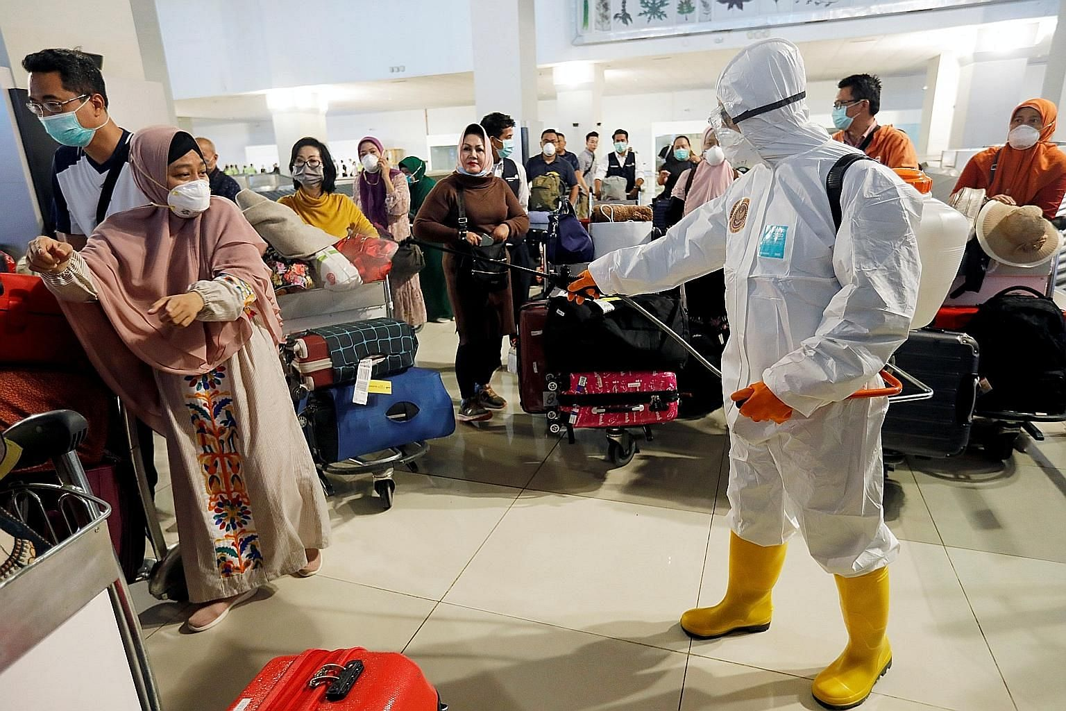 A worker spraying disinfectant on passengers' baggage at the international arrivals terminal of Soekarno-Hatta Airport near Jakarta, amid the coronavirus outbreak, last Thursday.