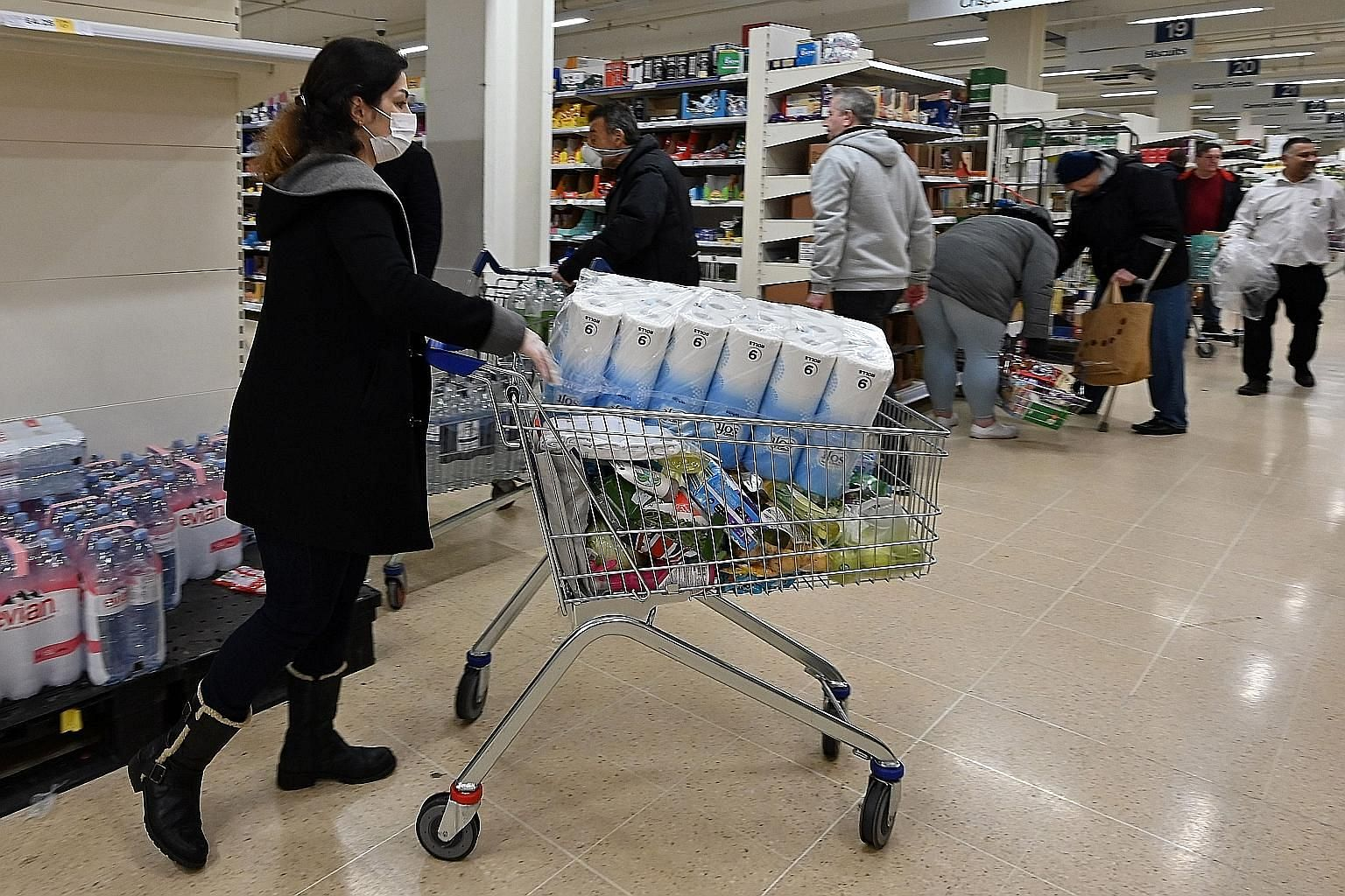 A woman wearing a face mask carting away toilet paper at a supermarket in London last Saturday. Consumers, worried about shortages during the pandemic, have started stockpiling household products.