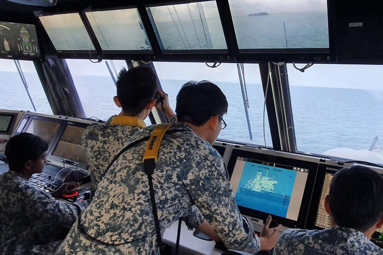 Navy personnel on board RSS Independence monitoring the Sam Jaguar, which was hit by pirates yesterday. PHOTO: MINDEF