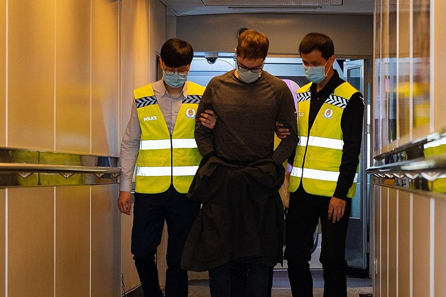 Canadian David James Roach, the suspect in a 2016 robbery of a Standard Chartered Bank branch in Holland Village, arriving in Singapore yesterday in the custody of the Singapore Police Force after he was extradited from Britain. He has been charged w