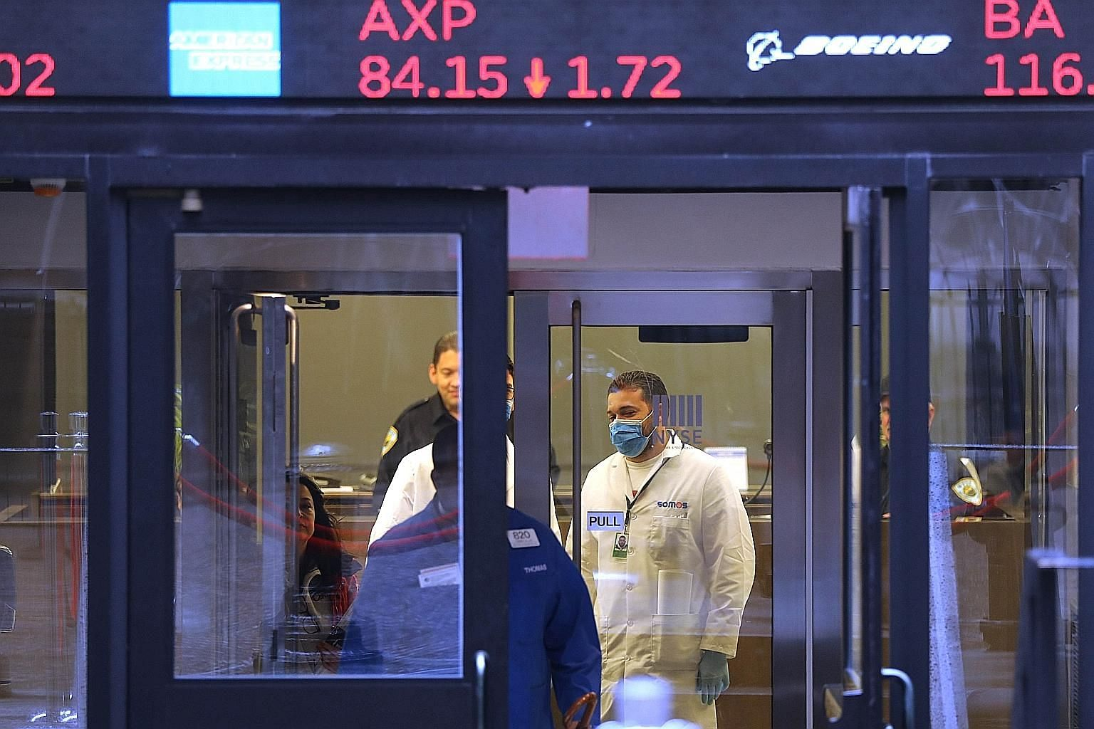 Medical personnel waiting to take the temperature of traders and others entering the New York Stock Exchange on Tuesday. The pandemic is not just a threat to health. It may also be a bigger economic threat than the financial crisis of 2008-2009.