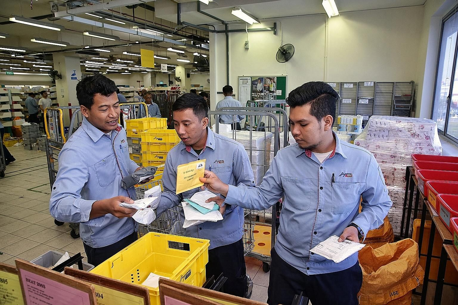 SingPost employees (from left) Hairul Azhar Ismail, 29, Mohammad Hussin Supardi, 30, and Mohd Syafiq Mohd Yusoff, 24, sorting mail for delivery at the Kallang Delivery Base yesterday. They are among about 400 Malaysian SingPost staff who are staying