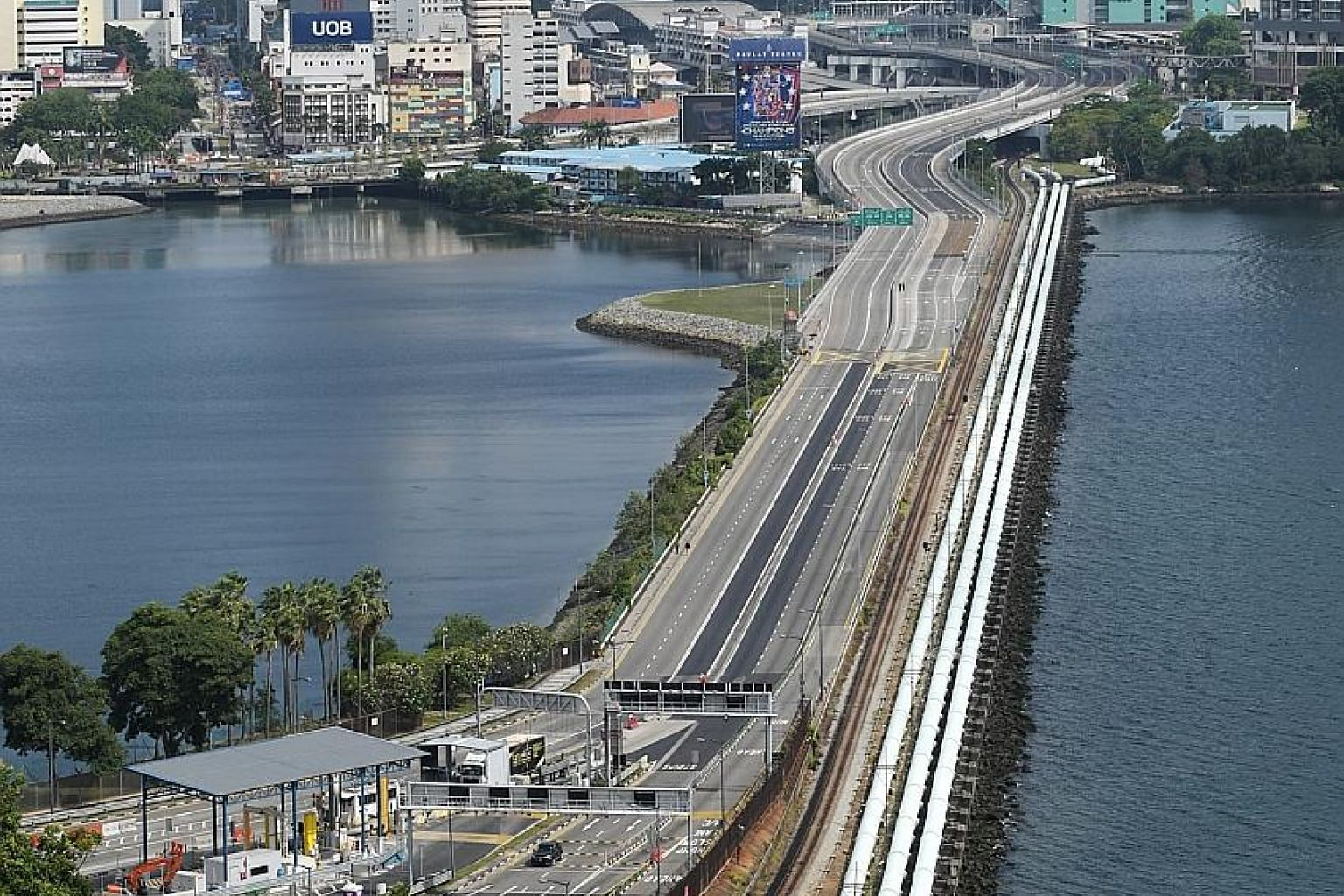 The Causeway between Johor and Singapore devoid of any vehicles at 10am yesterday, after Malaysia's movement control order took effect. However, movement of essential supplies across the border continued, with Trade and Industry Minister Chan Chun Si