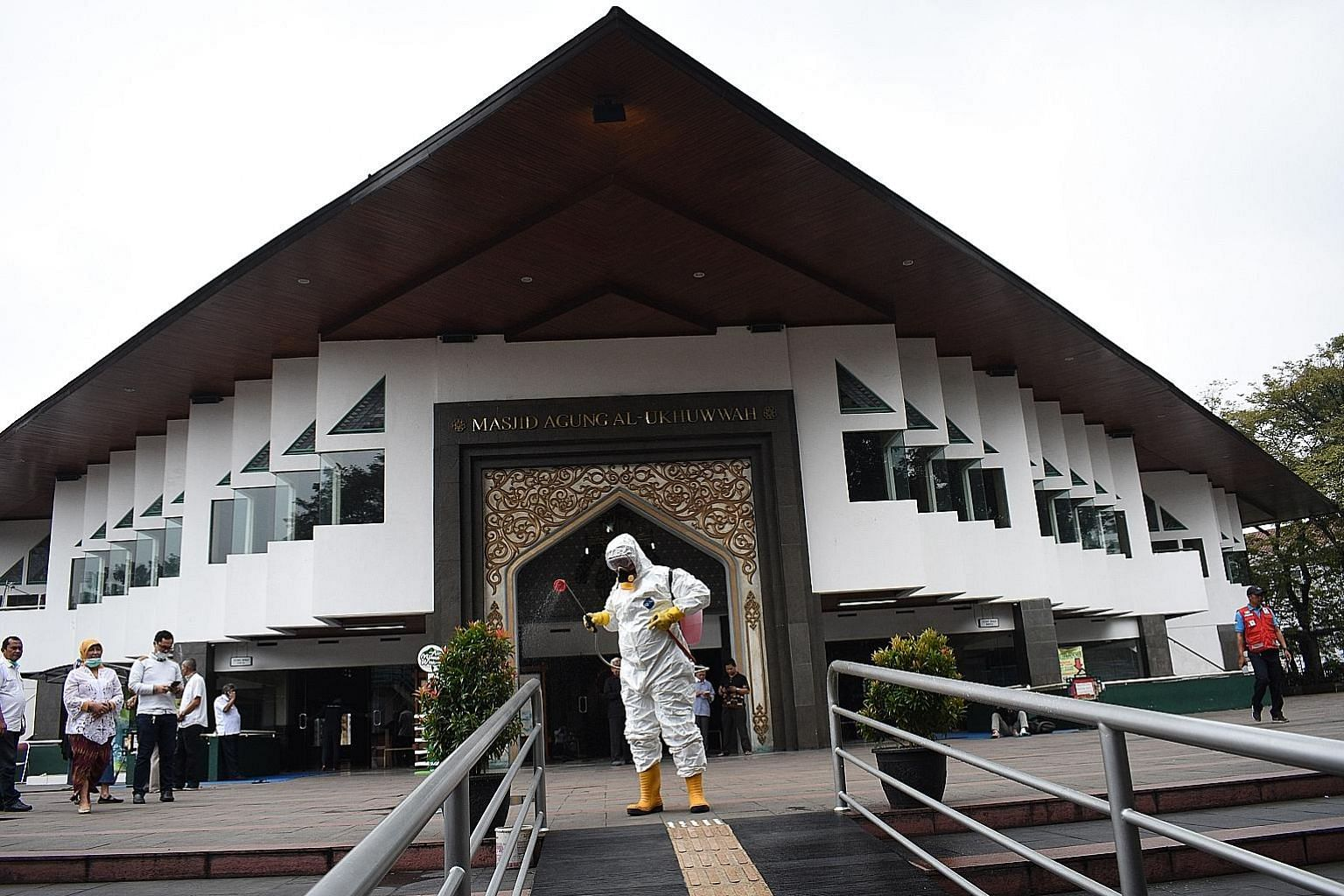 The premises outside a mosque in Bandung, West Java province, being sprayed with disinfectant yesterday. The number of deaths in Indonesia from the virus has risen by six to 25, most of which were in Jakarta. PHOTO: AGENCE FRANCE-PRESSE