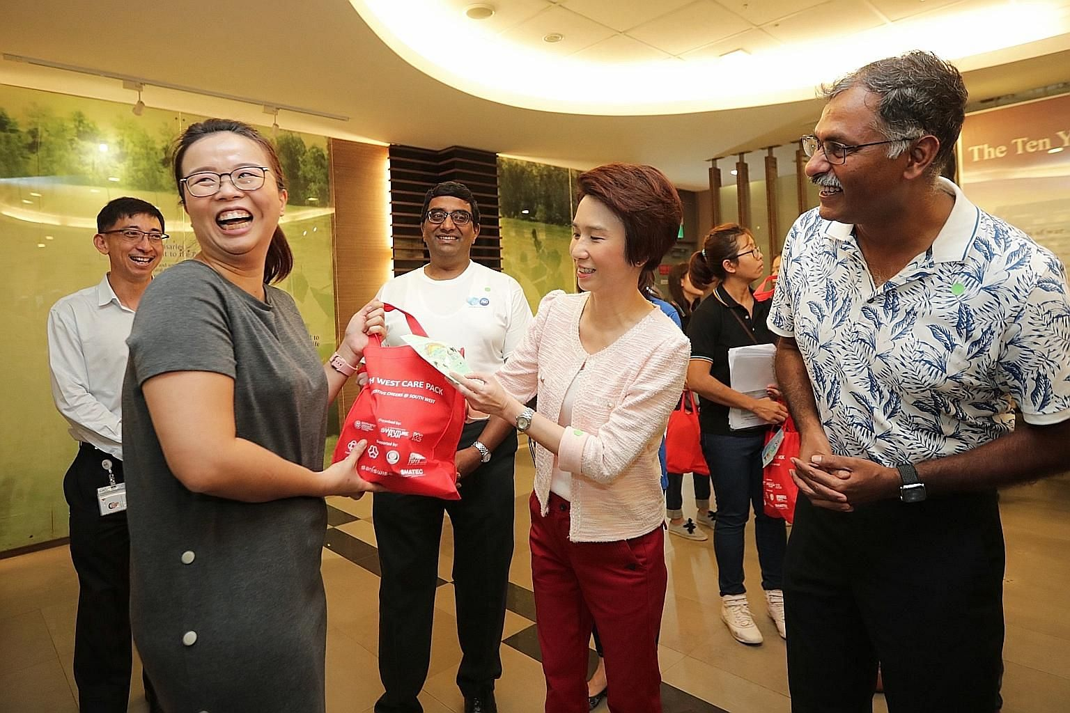 Ms Low Yen Ling, Mayor of South West District, giving out a care pack to Ms Lee Yanting, a 35-year-old medical technologist, at Bukit Batok Polyclinic yesterday. With them is Bukit Batok MP Murali Pillai (at right).