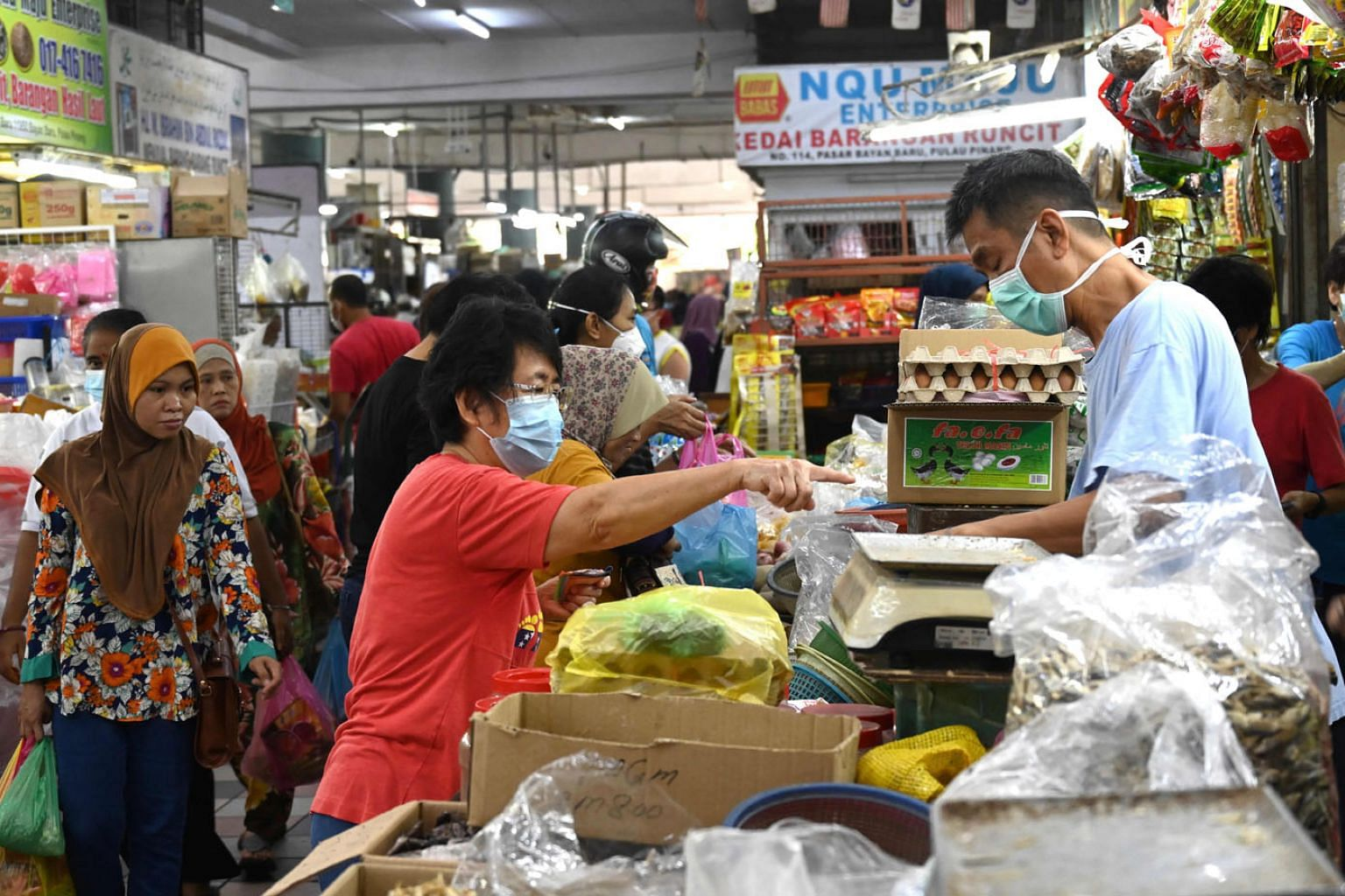 Shoppers buying fresh produce at a market in Penang on the third day of a partial lockdown in Malaysia yesterday. Except for essential services such as supermarkets, banks, petrol stations and pharmacies which will remain open, schools, offices, park