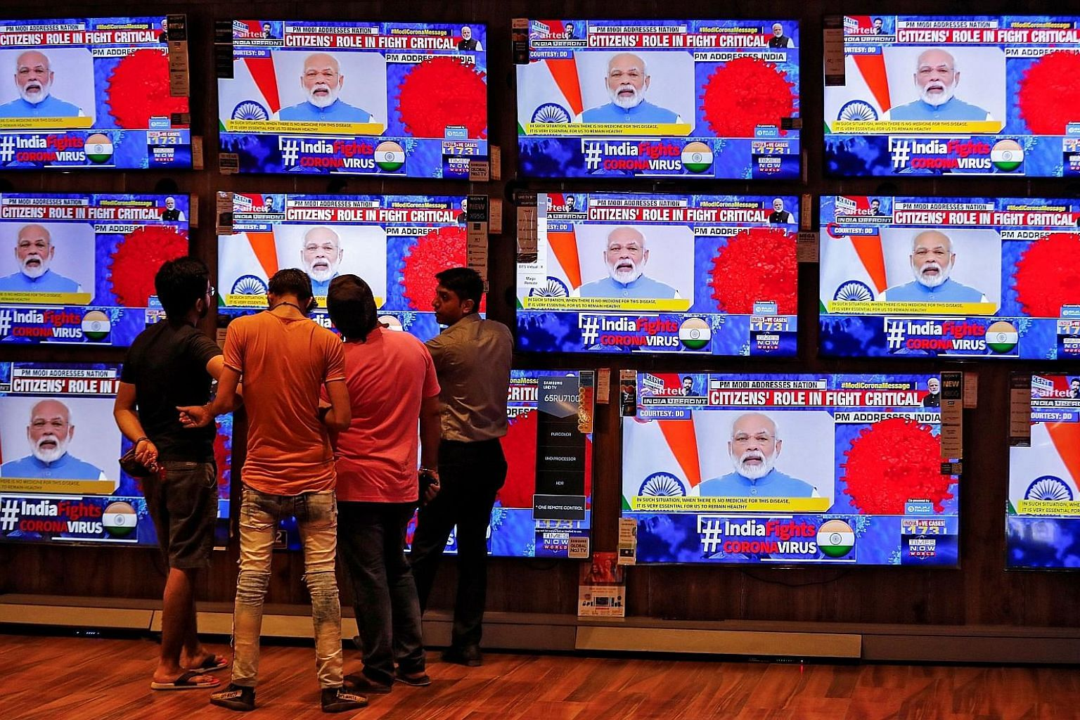 People in a showroom in Ahmedabad, India, on Thursday watching Indian Prime Minister Narendra Modi address the nation amid concerns about the coronavirus crisis. Mr Modi had earlier tried to get the leaders of member countries of the South Asian Asso
