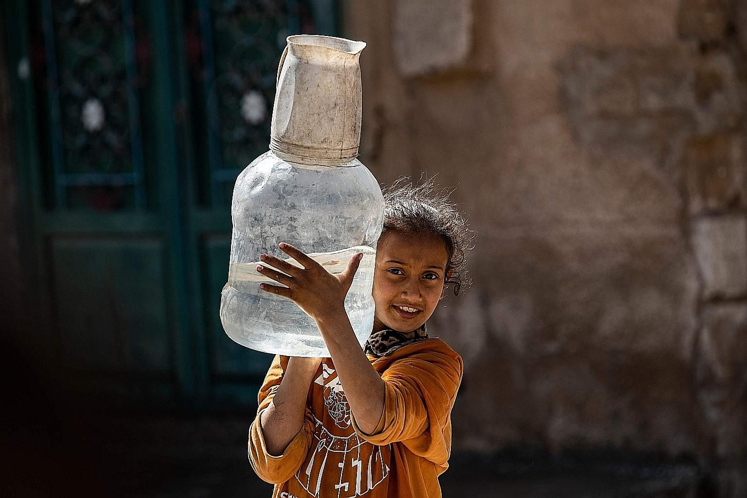 A girl carrying a container filled with water amid shortage in the Kurdish city of Al-Hasakah, in north-eastern Syria, earlier this month.