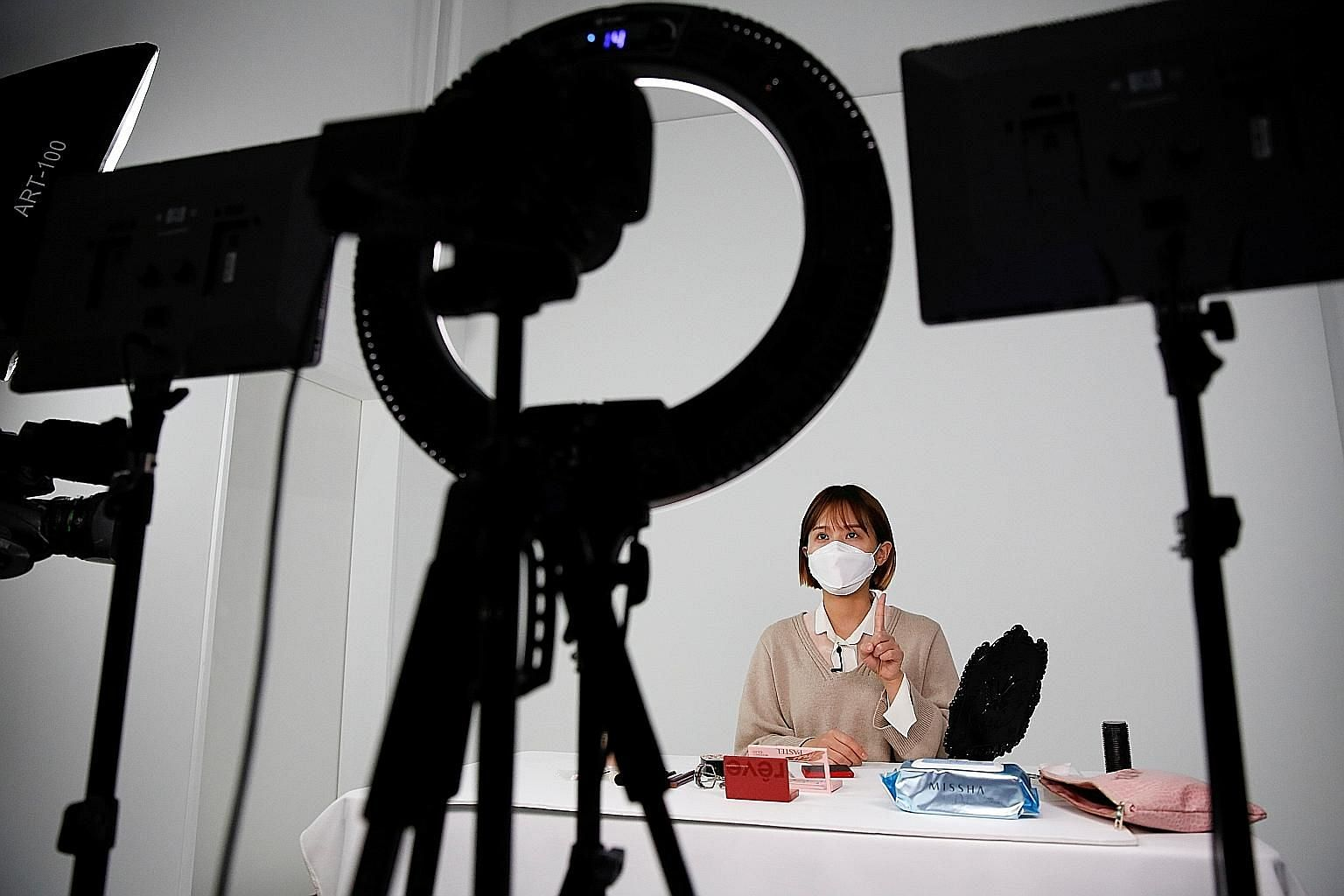 South Korean YouTuber Ssunzy (left) recording a video where she gives tips for applying make-up to look good with a mask and fashion designer Park Youn-hee (above) suggests wearing bold colours to stamp your individuality under the anonymity of a mas