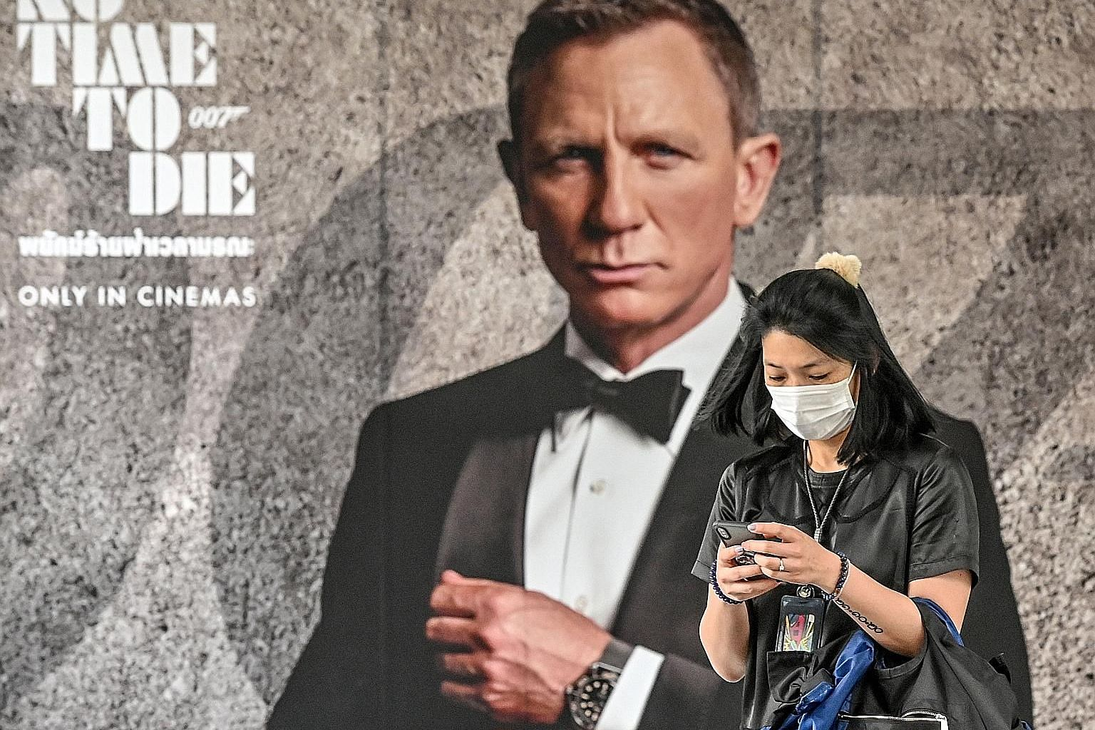 In this photo taken on Feb 28 in Bangkok, a woman walks past a poster for the upcoming James Bond movie No Time To Die, the release of which has been delayed due to the coronavirus pandemic. In A Quiet Place Part II, Emily Blunt (centre) and her fami