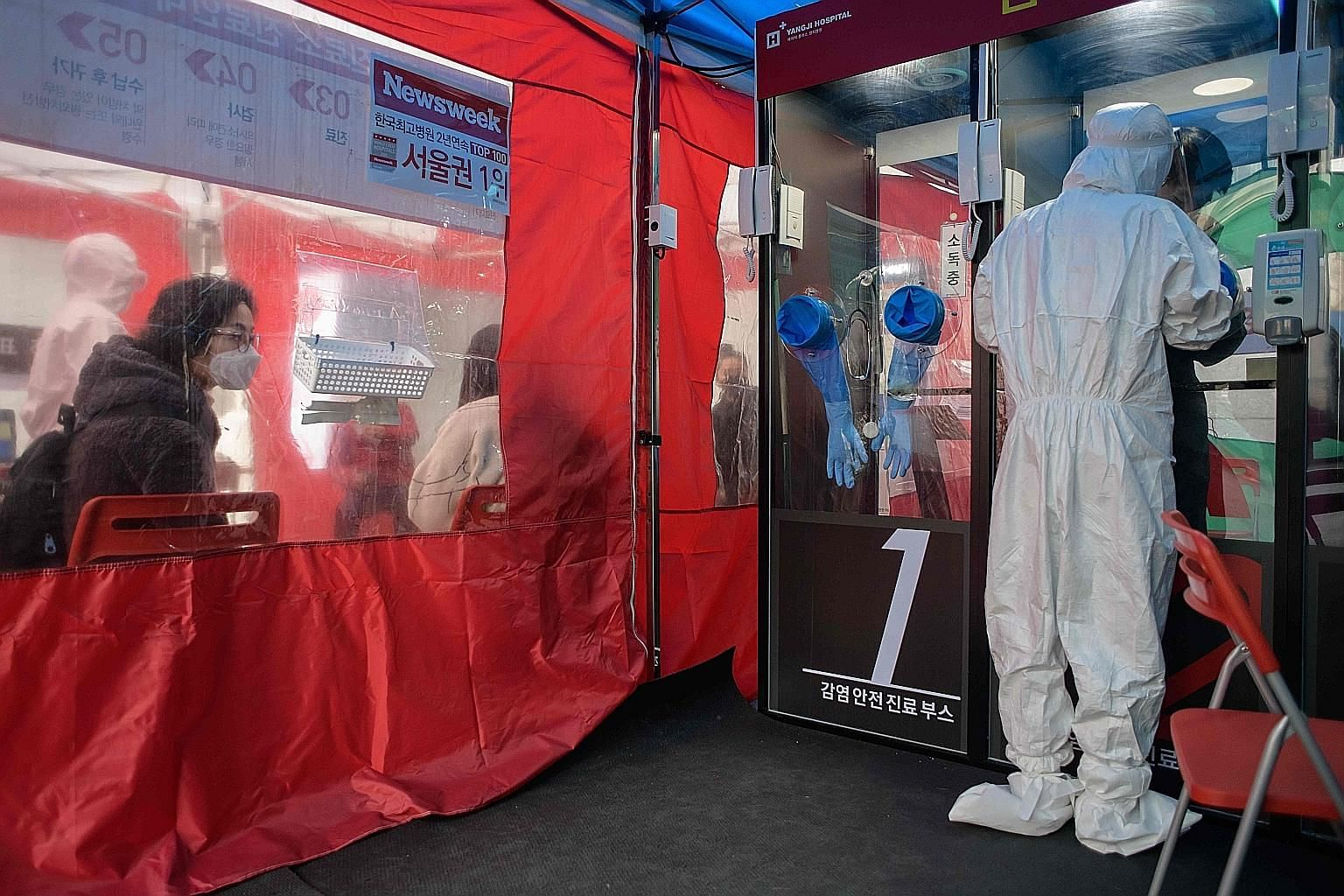 A woman watching from a waiting area as a nurse administers a coronavirus test at a booth outside Yangji Hospital in Seoul. Where China, Taiwan, Hong Kong and Singapore are better at adjusting to life with the virus, South Korea and Japan had more di