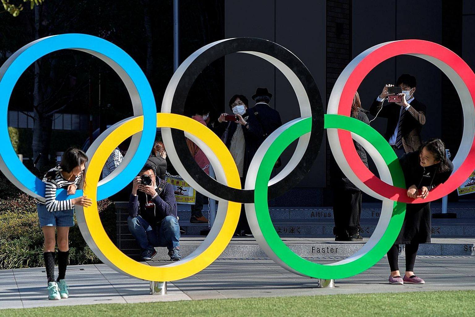 """Visitors posing at the Olympic rings in front of the Japan Olympic Museum in Tokyo, yesterday. The Tokyo 2020 Olympic Games have been delayed to """"a date beyond 2020 but not later than summer 2021"""". The new dates have not yet been set."""