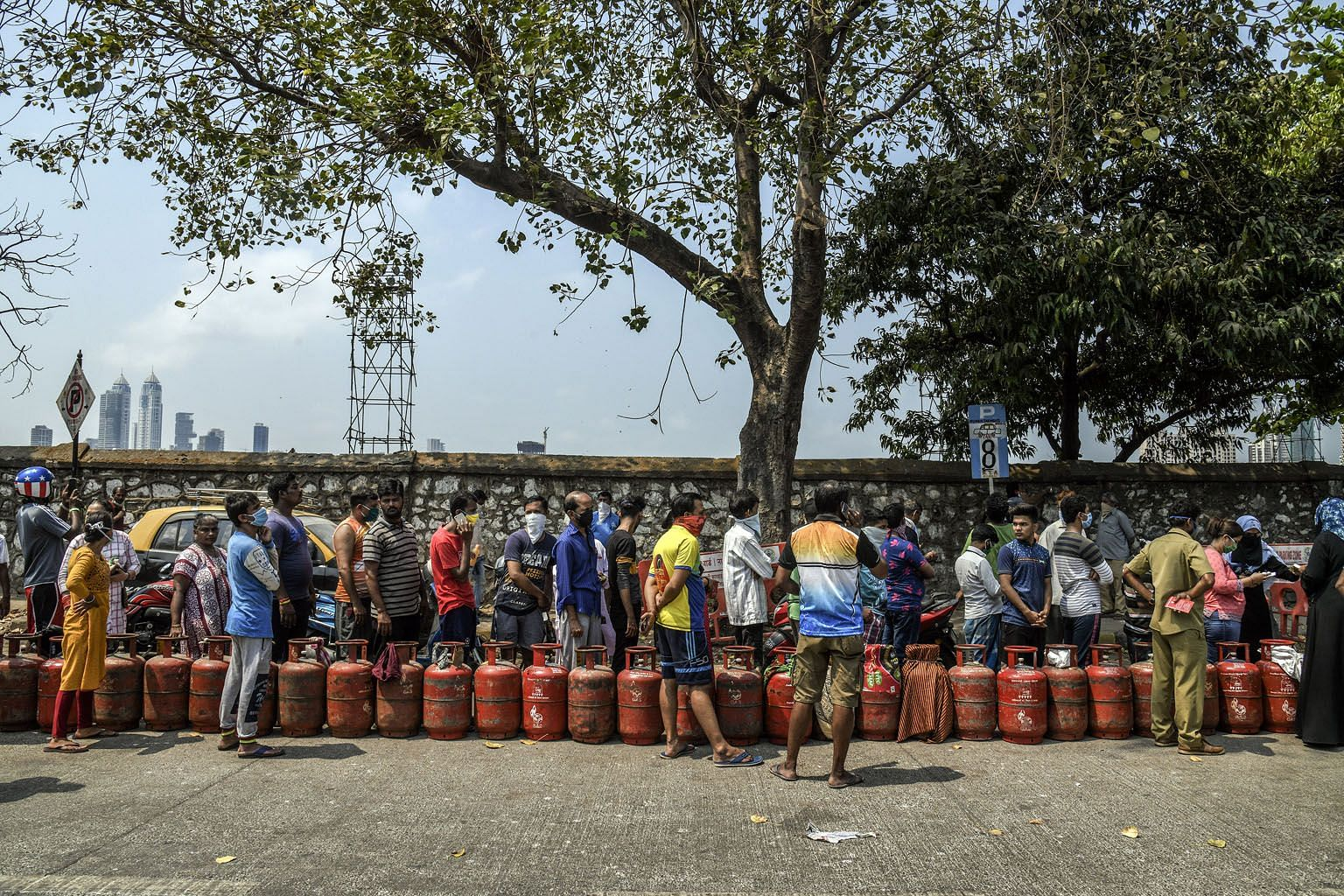 People waiting to purchase cooking gas in Mumbai on Wednesday. India went into lockdown from midnight on Tuesday to prevent the further spread of Covid-19. The complete cessation of economic activity is hitting the poor the hardest.