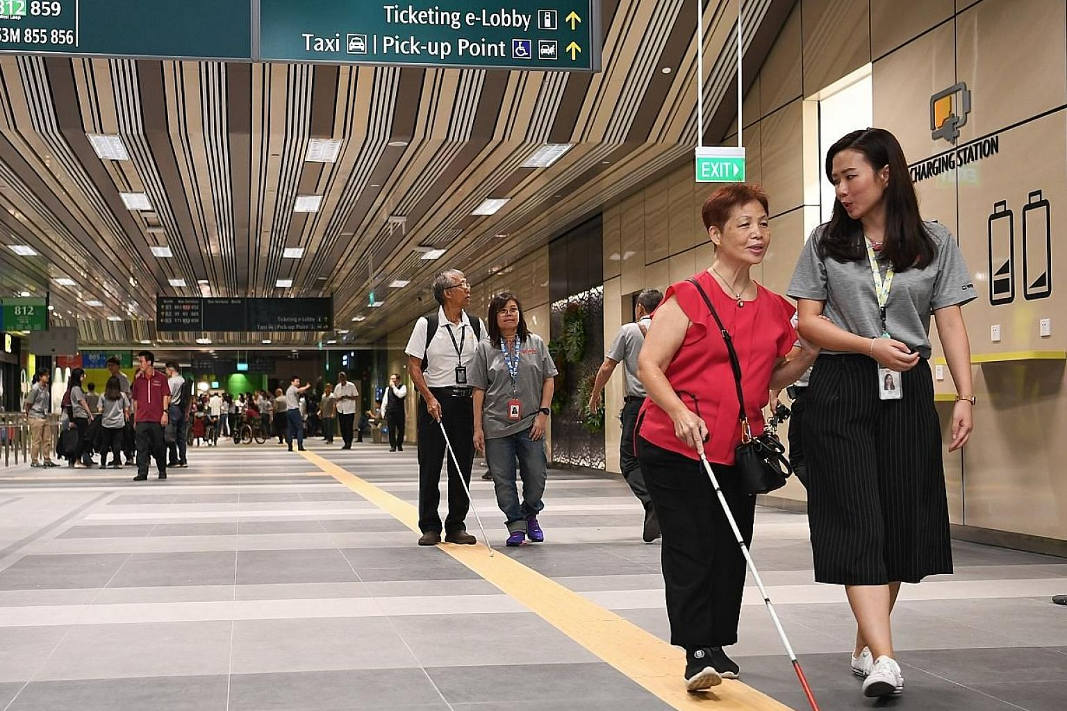 People with visual impairment being guided by SMRT staff at the Yishun Integrated Transport Hub last year. Social distancing does not prevent us from bridging the gap with a vulnerable person to offer help, the writer says. ST FILE PHOTO
