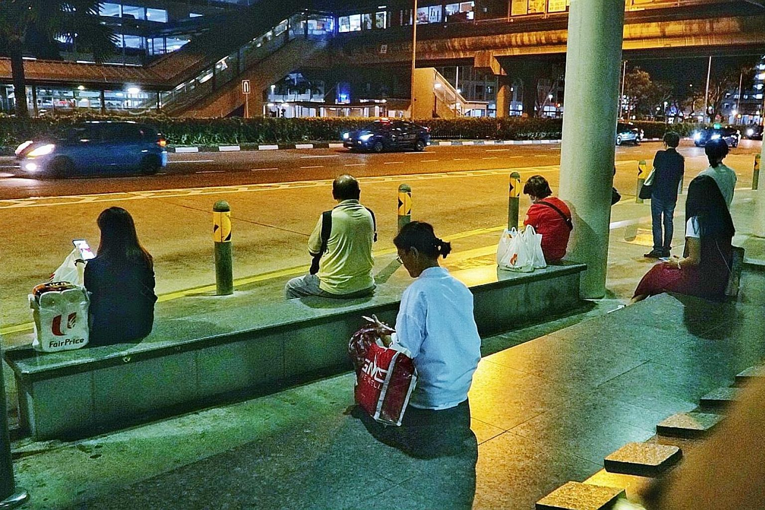 Commuters observing safe distancing at a bus stop near Admiralty MRT station. As Singapore battles a second surge of Covid-19 cases, many of whom are returning residents or long-term pass holders, bars and other entertainment outlets have been ordere