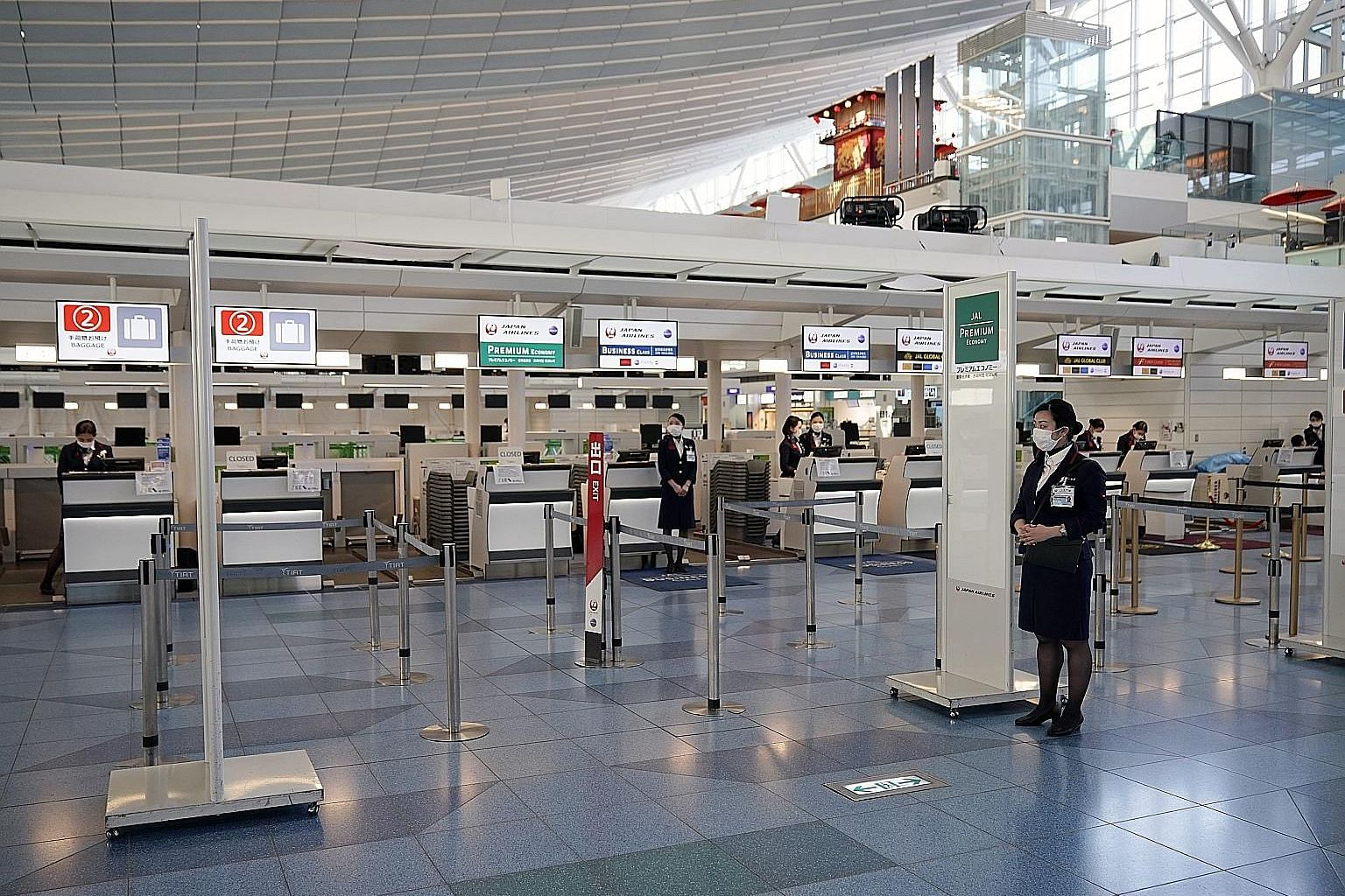 Japan Airlines ground staff wearing face masks at Haneda Airport earlier this month. The coronavirus crisis led to a 58.3 per cent plunge in tourist arrivals in Japan last month, and this is set to worsen with the worldwide travel restrictions that a