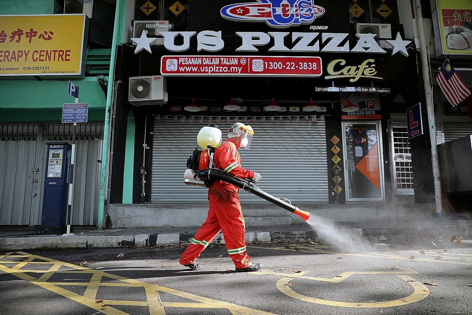 A worker spraying disinfectant on a street in Kuala Lumpur yesterday, while the movement control order is in place due to the coronavirus outbreak. Malaysia on Friday unveiled a RM250 billion (S$83.4 billion) stimulus package to cushion the country's