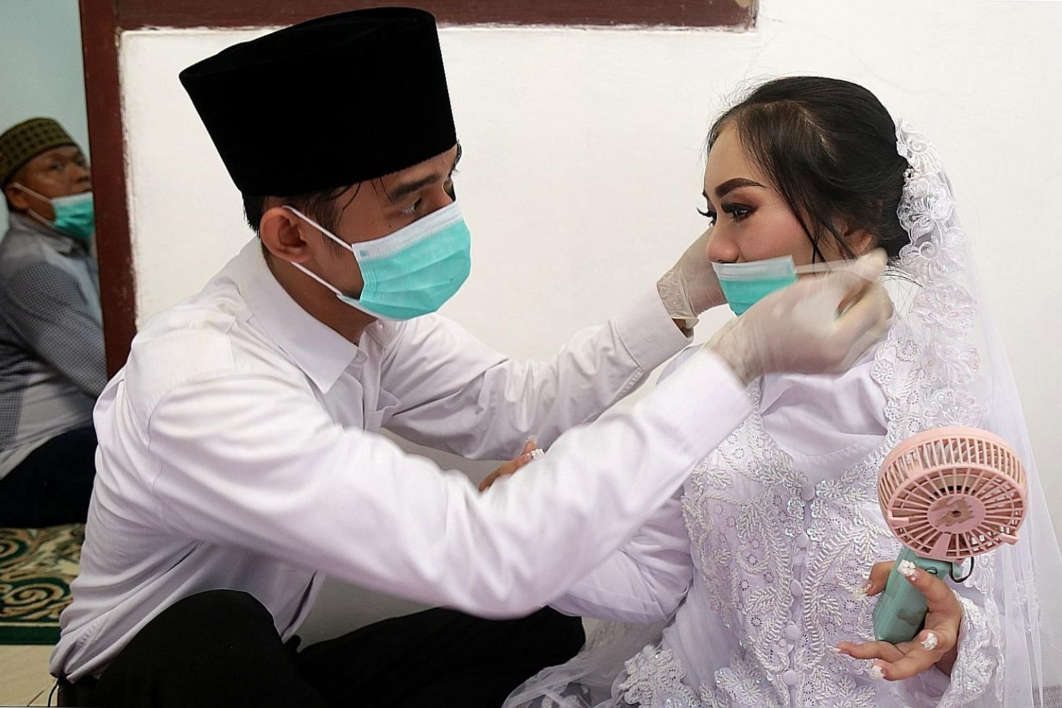 A groom puts a face mask on his bride before their wedding ceremony in Jakarta. The wedding proceeded on Saturday amid concerns about the coronavirus outbreak, which has led the government to consider a lockdown of the capital.