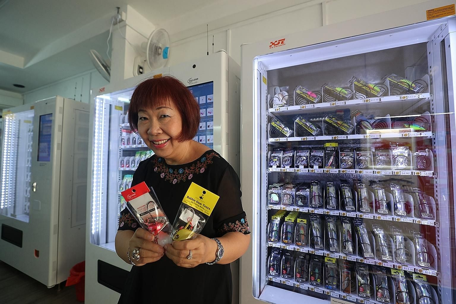 Ms Elizabeth Lai with fishing tackle that can be purchased from vending machines at her Clementi West shop. ST PHOTO: TIMOTHY DAVID