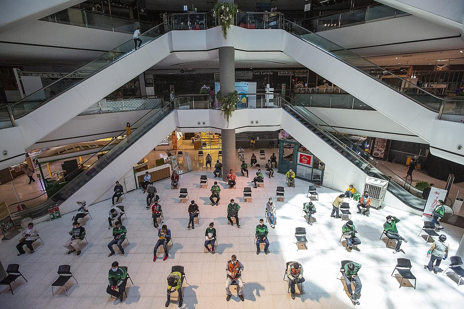 Food delivery couriers keeping a distance from one another while waiting at the Central Plaza Pinklao mall during a partial lockdown in Bangkok yesterday. With over 1,500 cases of coronavirus infections recorded in Thailand so far, even relaxed folk