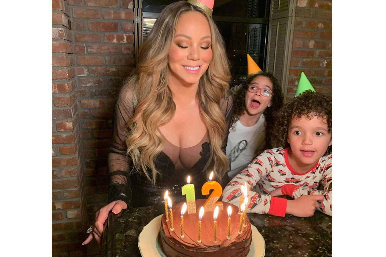 """ETERNALLY 12"": American singer Mariah Carey may have turned 50 last Friday, but she is still young at heart. The singer posted on Instagram a photo of herself with a birthday cake and her 8½-year-old twins standing behind her. It was captioned: ""Sp"