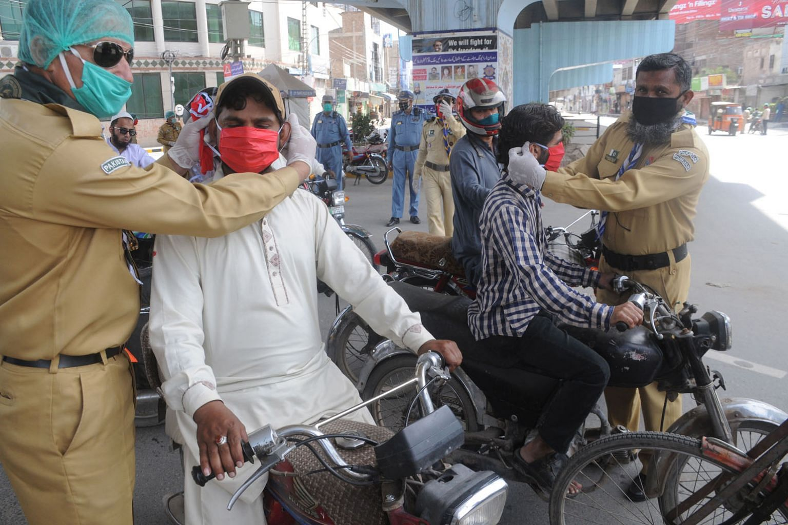 Volunteers distributing face masks to people during a partial lockdown in Multan, Pakistan, on Sunday. Public health infrastructure in India, Pakistan or any number of sub-Saharan African countries is already struggling to cope, even at this relative