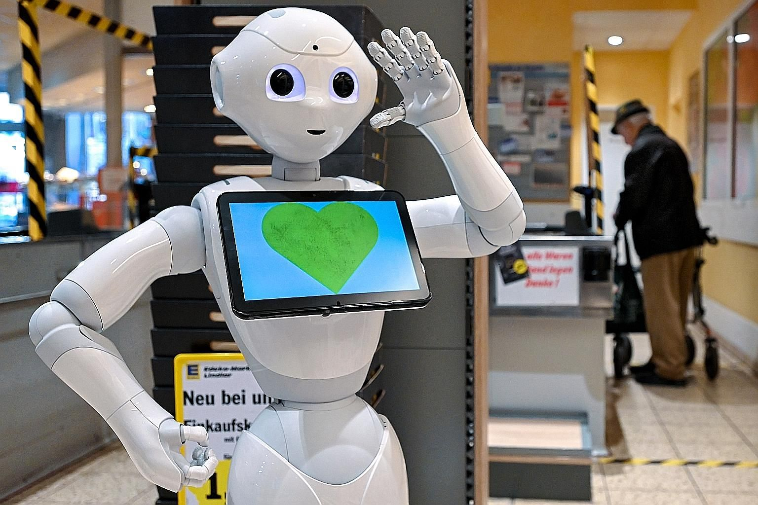 "A humanoid robot named ""Pepper"" reminding customers at a German supermarket to keep a safe distance from one another to minimise the transmission of the coronavirus."
