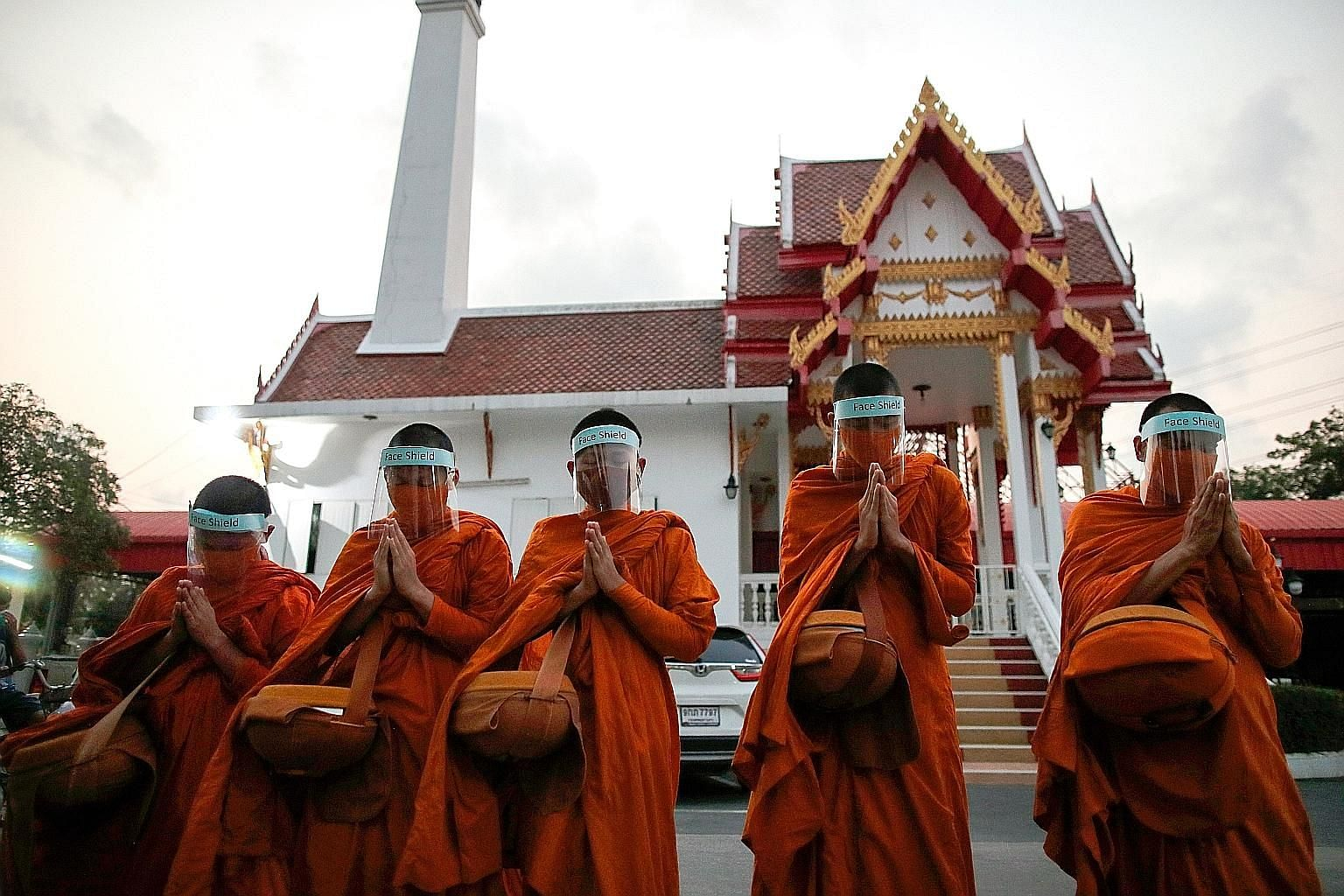 Buddhist monks wearing masks and face shields as they collected alms in Bangkok on Tuesday. PHOTO: EPA-EFE