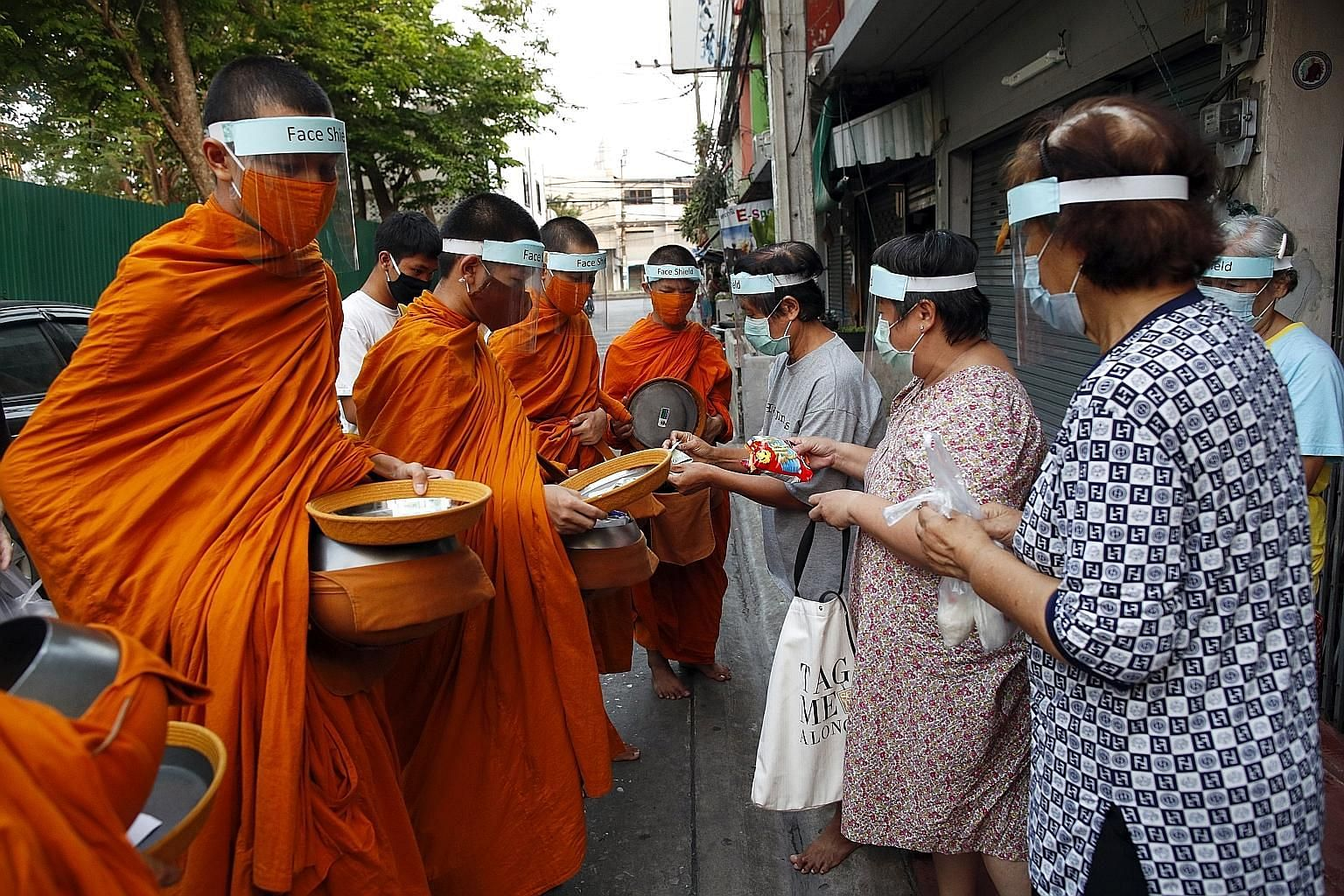 Buddhist monks from Wat Matchantikaram temple wearing masks and face shields receiving alms in Bangkok on Tuesday. The shop closure order announced yesterday is the latest in the series of gradual closures of various venues and restrictions in Bangko