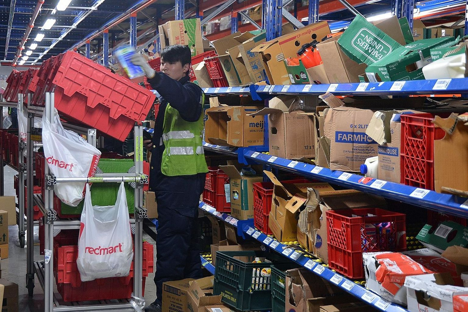 E-grocer RedMart has started prioritising the sale of daily essentials such as milk powder and rice and made changes to its logistics to cater to the rising demand. ST FILE PHOTO
