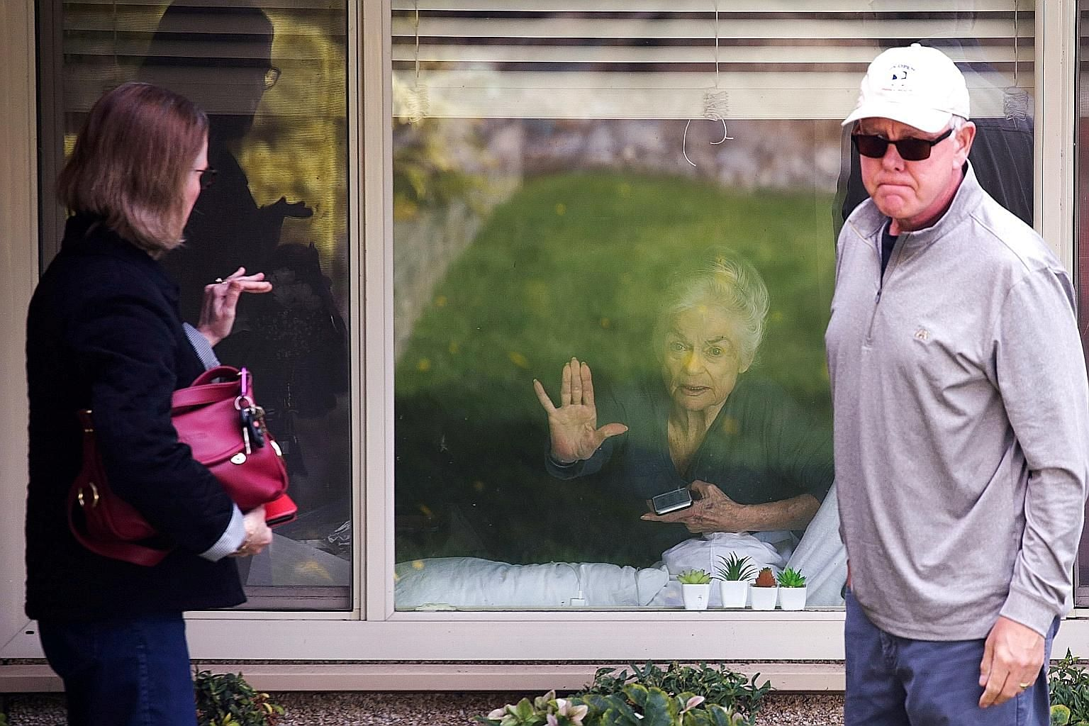 Ms Judie Shape, 81, who tested positive for coronavirus, waving goodbye to her daughter Lori and son-in-law Michael Spencer who visited outside her room at Life Care Centre in Kirkland, Washington. The facility was the epicentre of an outbreak in the