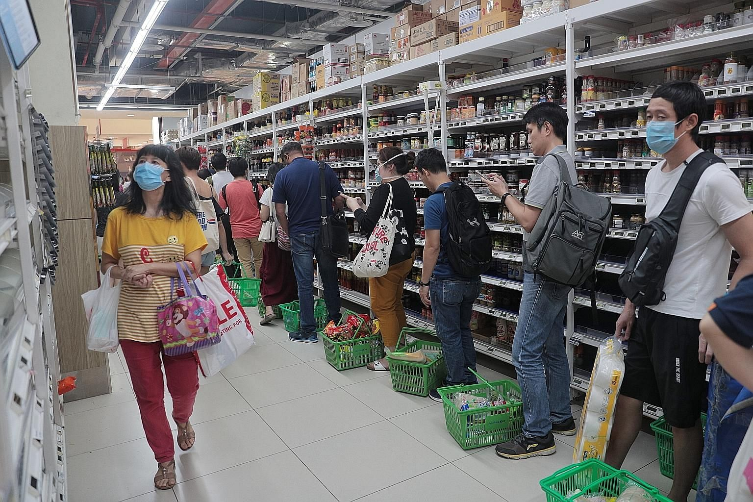 A queue of shoppers at FairPrice supermarket in Jem mall at about 6.20pm yesterday, after stricter measures were announced to curb the spread of the coronavirus. FairPrice said it is getting more manpower for crowd control and to help existing staff.