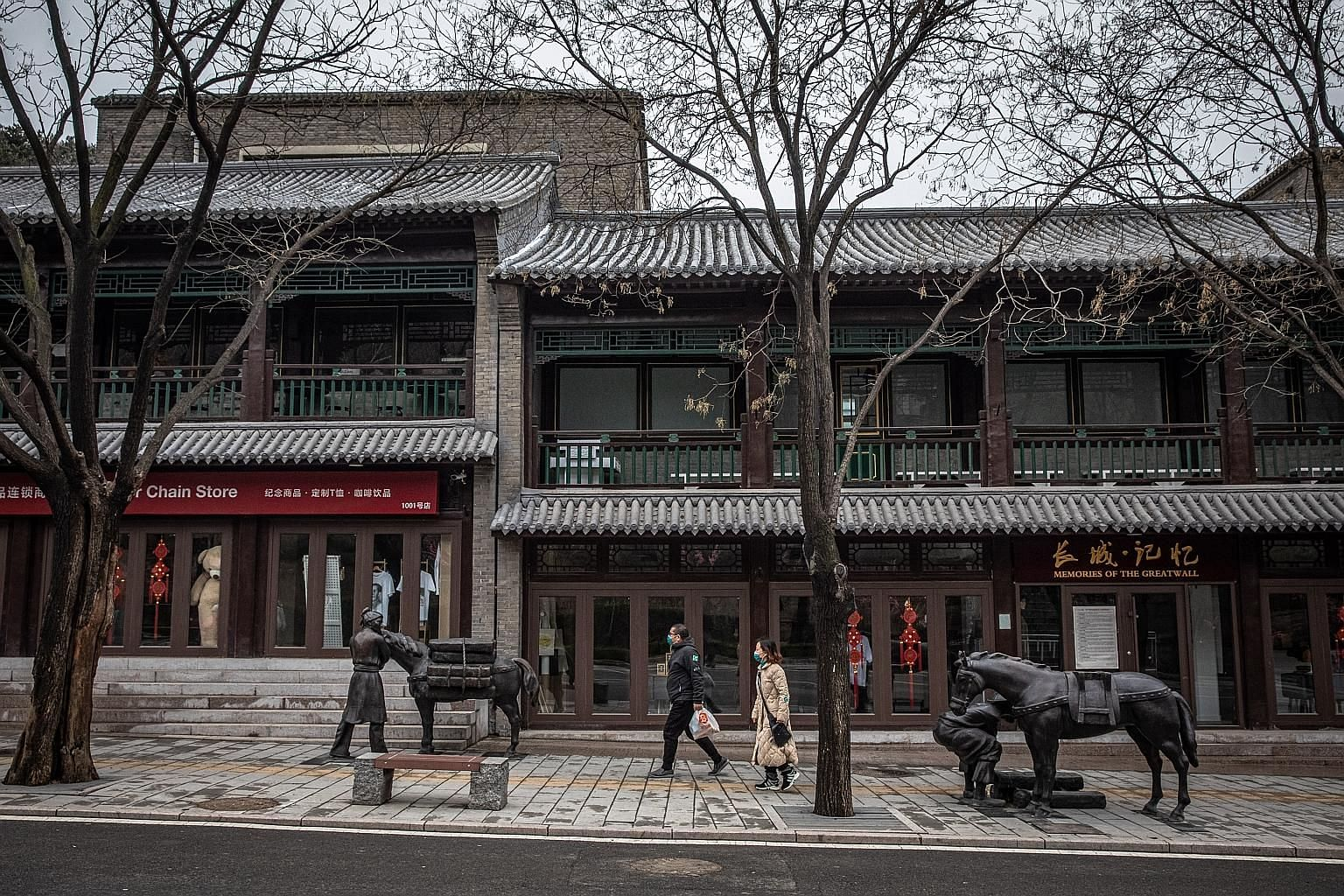 Tourists wearing protective face masks walk past closed restaurants and shops at the Badaling Great Wall area, in Beijing. The service sector is an important generator of jobs in China and accounts for about 60 per cent of its economy, which now look