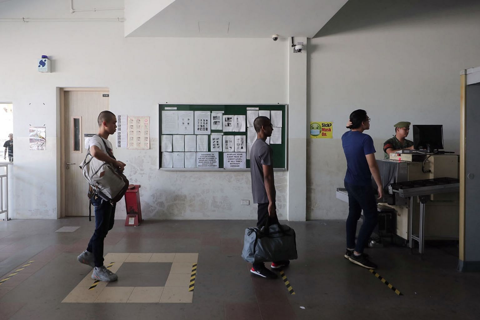 Newly enlisted national servicemen queueing for security checks while practising social distancing at the SAF Ferry Terminal before heading to Pulau Tekong on Wednesday. Defence Minister Ng Eng Hen said yesterday that the SAF has to continue to safeg