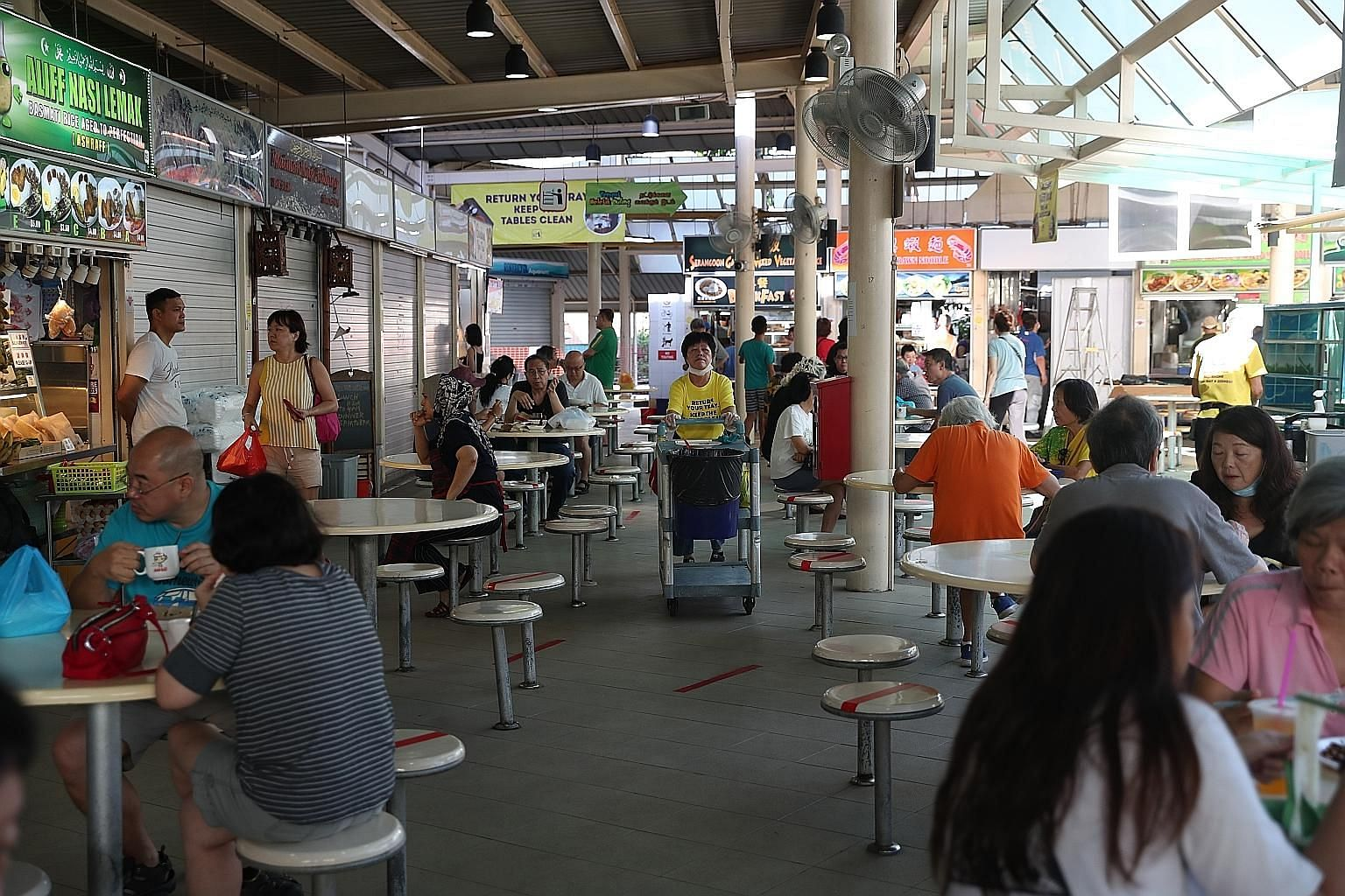 Diners observing social distancing at Serangoon Garden food centre. While takeaways will still be allowed when the ban on eating out kicks in on Tuesday, operators worry that business will slow to unsustainable levels as workplaces close and Singapor