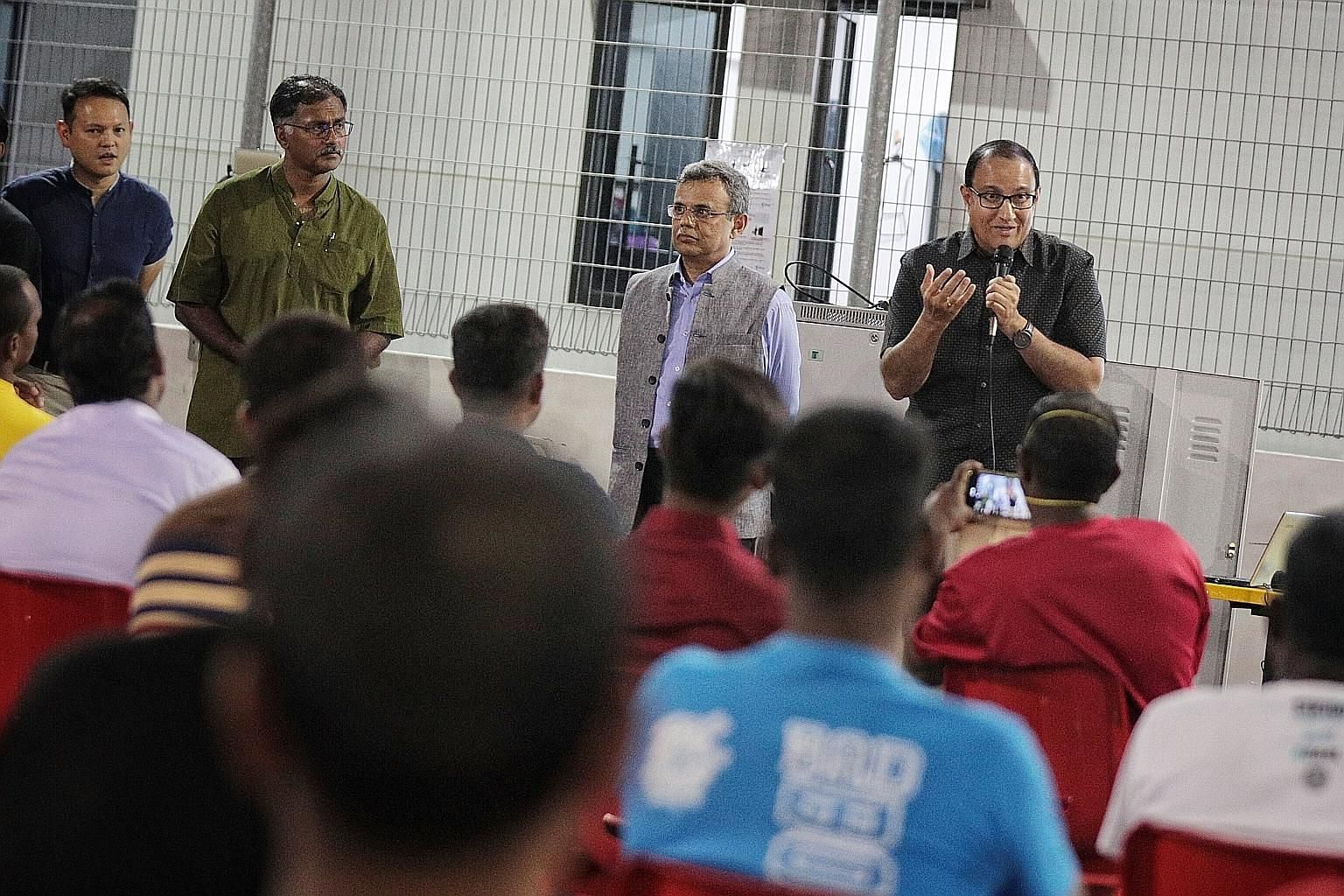 Minister for Communications and Information S. Iswaran (far right) speaking to migrant workers to assuage their concerns at Westlite Papan dormitory in Jurong yesterday. With him are (from left) Minister of State for Manpower Zaqy Mohamad, Bukit Bato