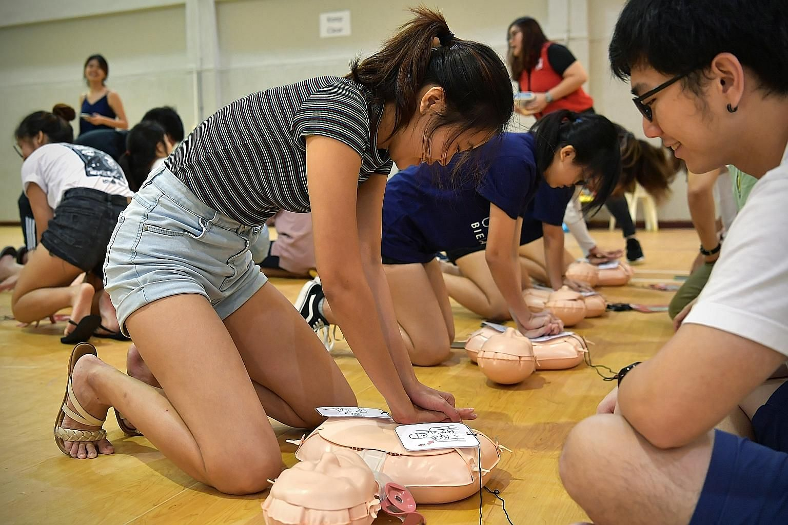 Participants practising cardiopulmonary resuscitation on dummies with Red Cross instructors at a life-saving workshop organised by a group of Nanyang Technological University communication students on Feb 27.