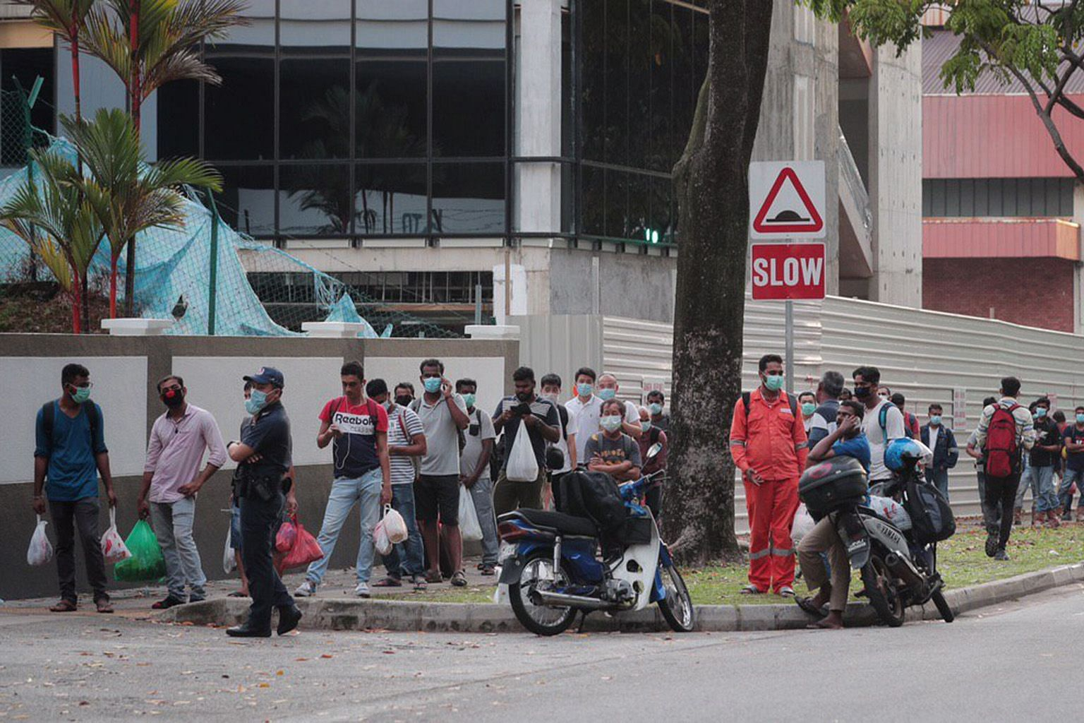 Above: Migrant workers returning yesterday to the Westlite Toh Guan dormitory. Some 6,800 of them have been told to stay in their rooms for 14 days. ST PHOTO: JASON QUAH Left: Workers at the S11 Dormitory @ Punggol yesterday. It has 63 virus cases. W