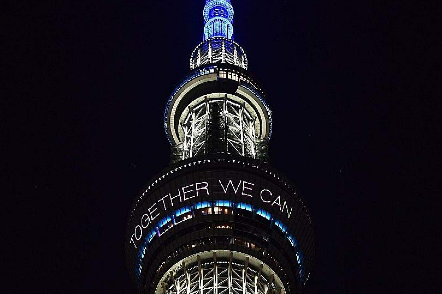 """The Tokyo Skytree all lit up and sending an encouraging """"Together we can all win!"""" message amid the pandemic."""