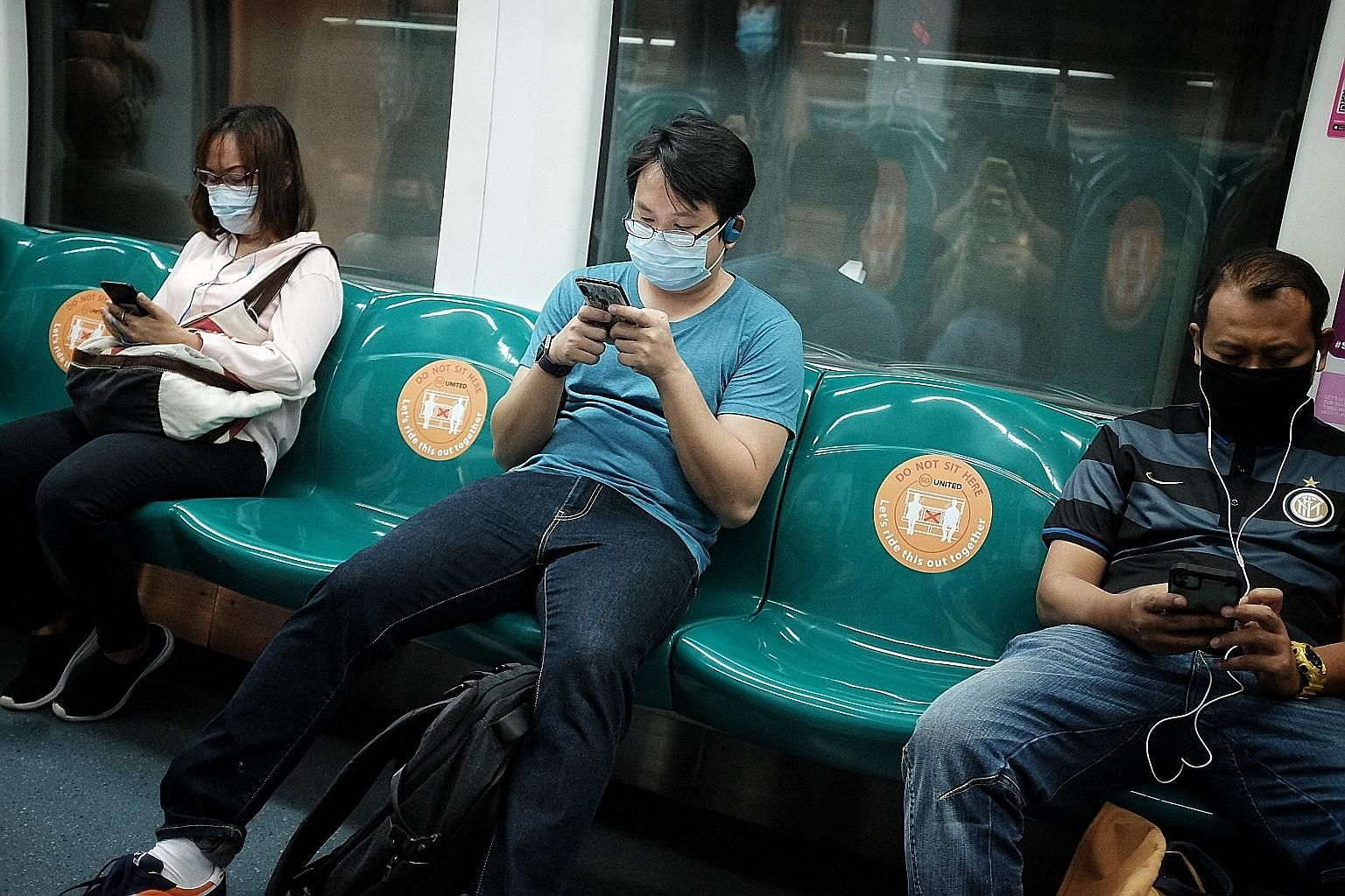 MRT commuters observing safe distancing at about 9.30am yesterday. Standing spaces and seats that should be avoided will be marked out with stickers, and thermal scanners will be deployed at selected MRT stations.