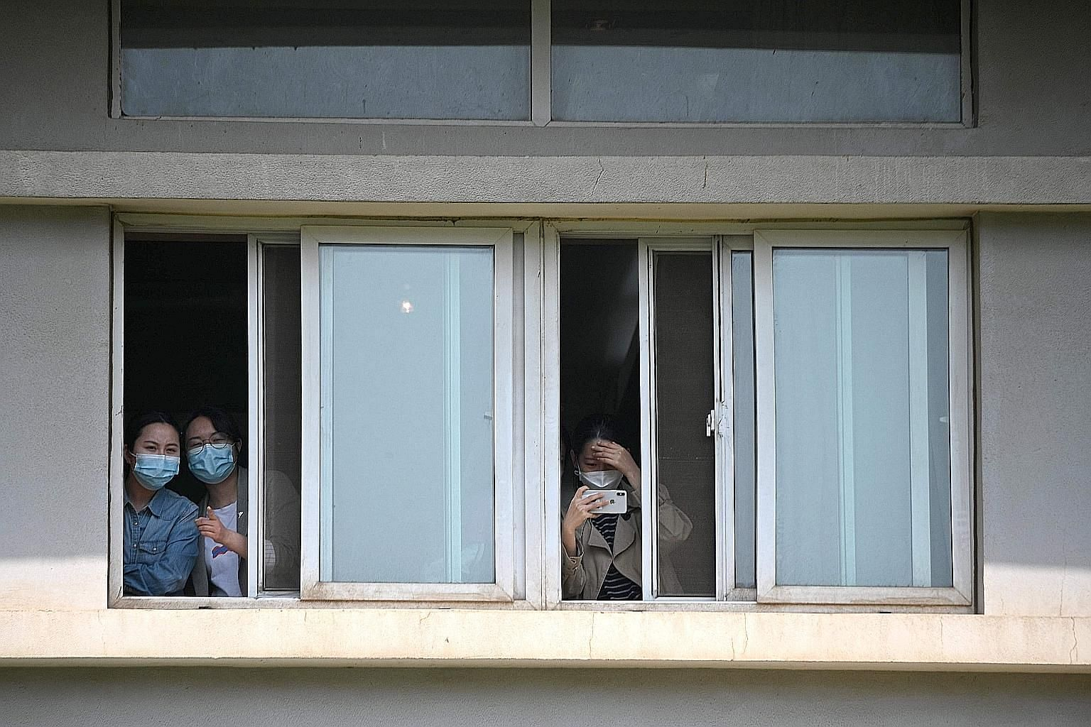 """People with face masks peeking from windows of the Jinyintan Hospital in Wuhan, China's central Hubei province, yesterday. Dubbed """"ground zero"""" at the height of the coronavirus outbreak in the city, Jinyintan is the only specialised infectious diseas"""