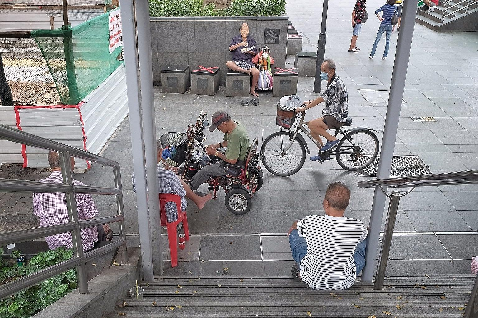 A group of men sitting at a flight of stairs in Chinatown yesterday afternoon. The circuit breaker measures can work only if everyone plays his or her part. More than 1,900 people have been infected, and six have died. A group of men chatting outside